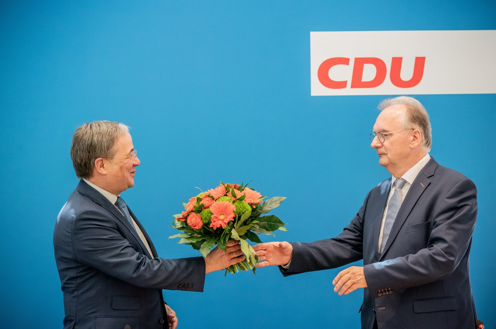 Armin Laschet (L), the state premier of North-Rhine Westphalia (NRW) and leader of the Christian Democratic Union party (CDU), hands a bouquet of flowers to Saxony-Anhalt State Premier Reiner Haseloff at a CDU board meeting following the Saxony-Anhalt state election, in Berlin, Germany, June 7, 2021. (Reuters Photo)
