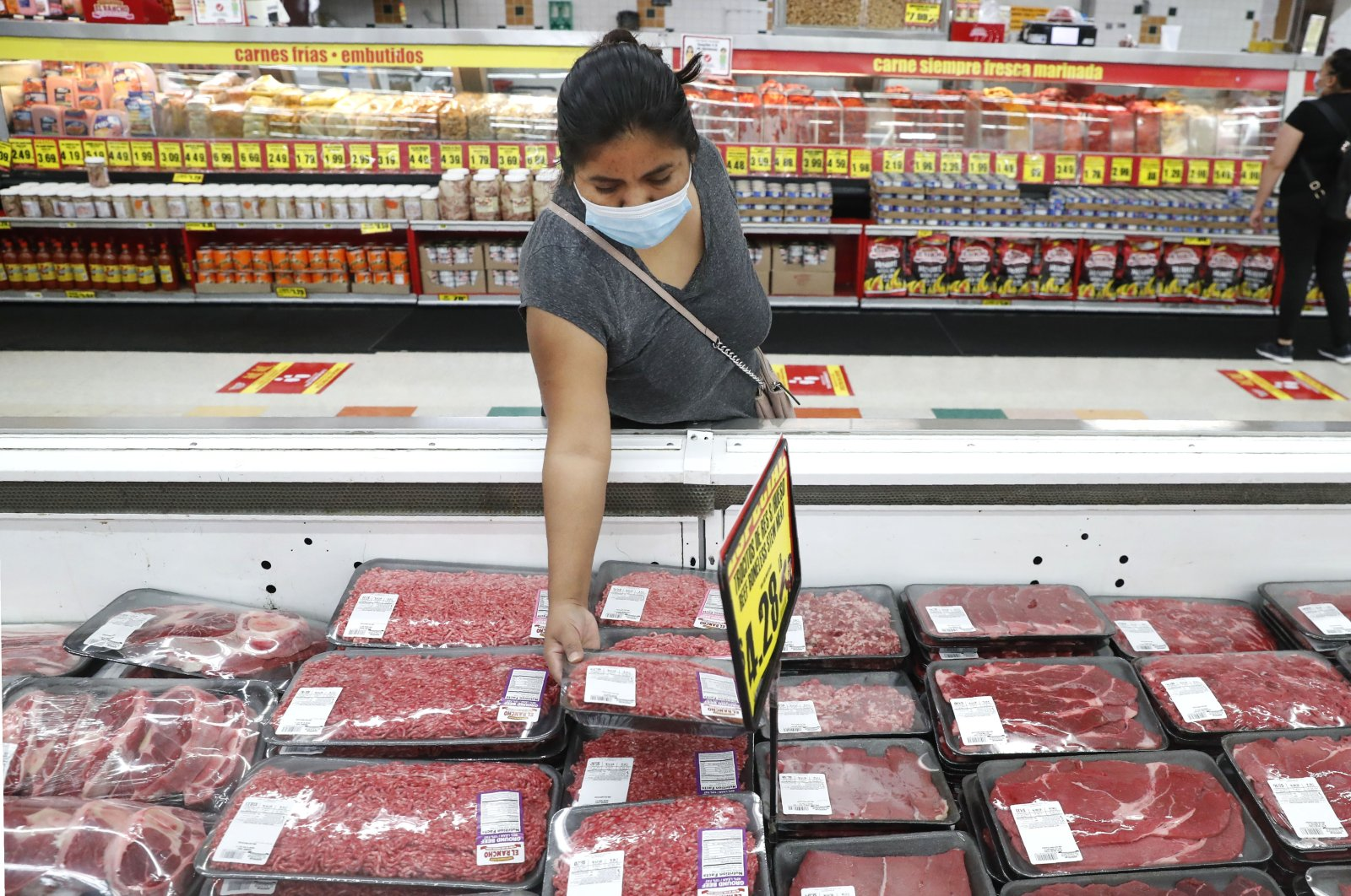 A shopper wears a mask as she looks over meat products at a grocery store in Dallas, Texas, U.S., April 29, 2020. (AP Photo)