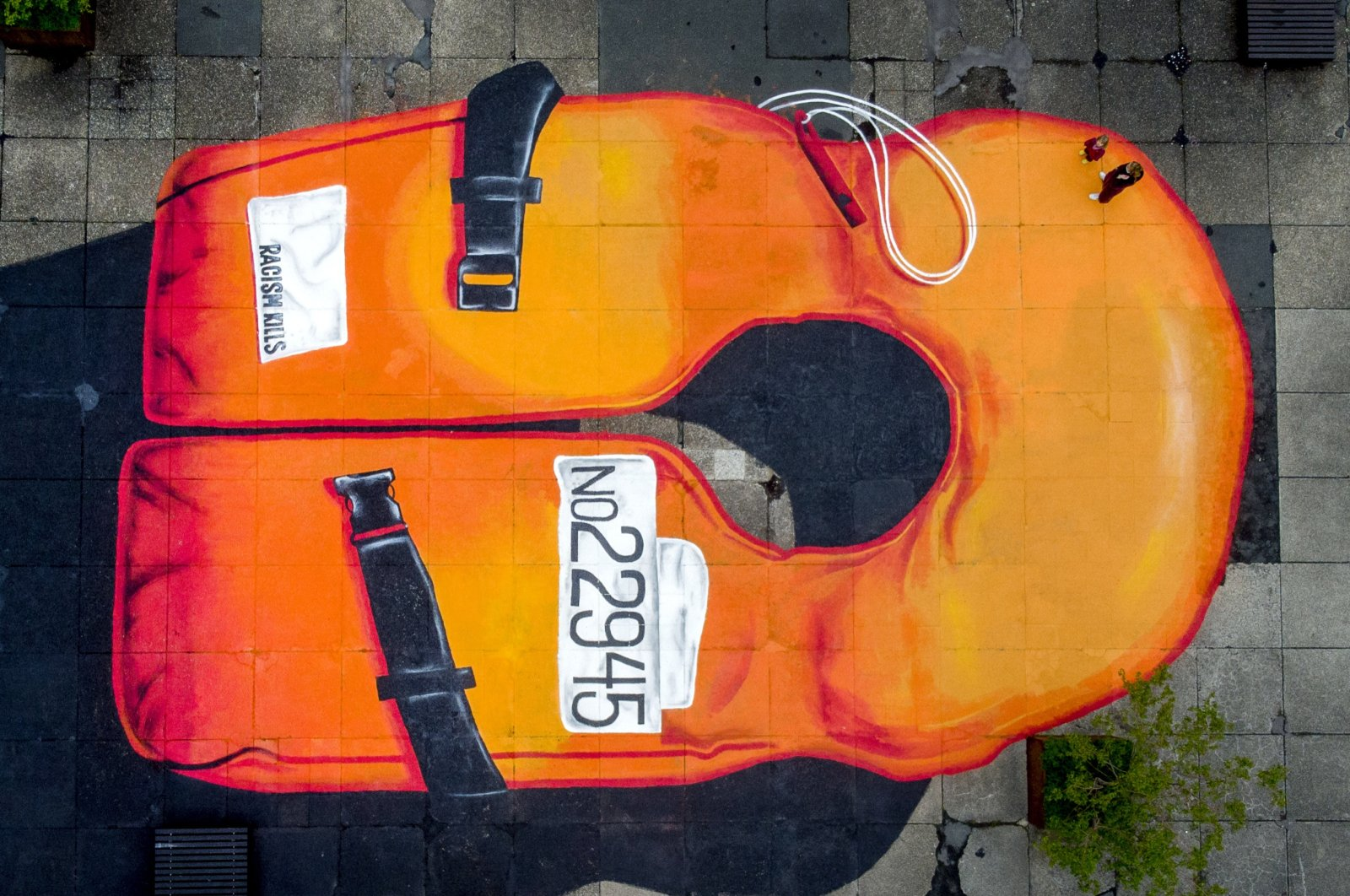 A 12 x 20 meter painting of a life jacket set on the grounds of a university campus in Frankfurt, Germany, May 27, 2021. (AP Photo)