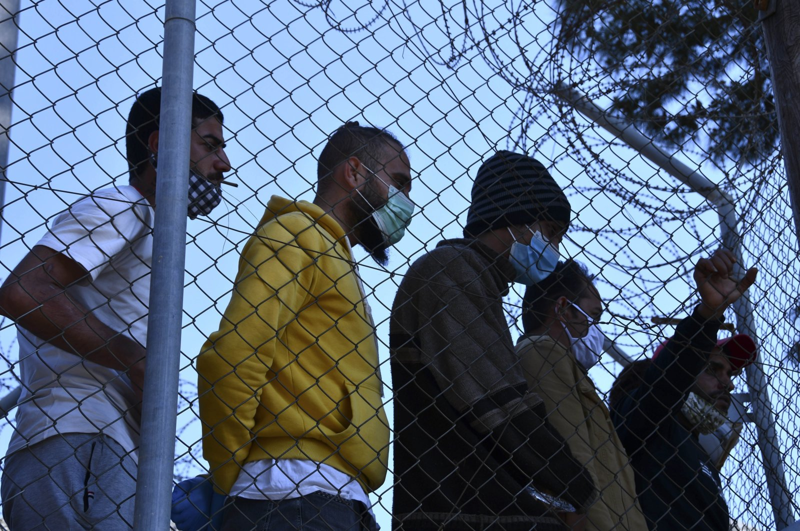 Migrants inside a refugee camp watch European Union Commissioner Ylva Johansson's visit to the port of Vathy on the eastern Aegean island of Samos, Greece, March 29, 2021. (AP Photo)