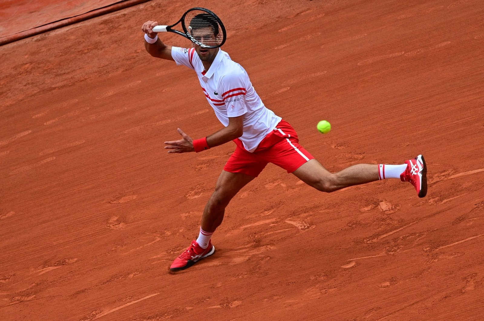 Serbia's Novak Djokovic returns the ball to Italy's Lorenzo Musetti during their men's singles fourth round tennis match on Day 9 of The Roland Garros 2021 French Open tennis tournament in Paris, France, June 7, 2021. (AFP Photo)