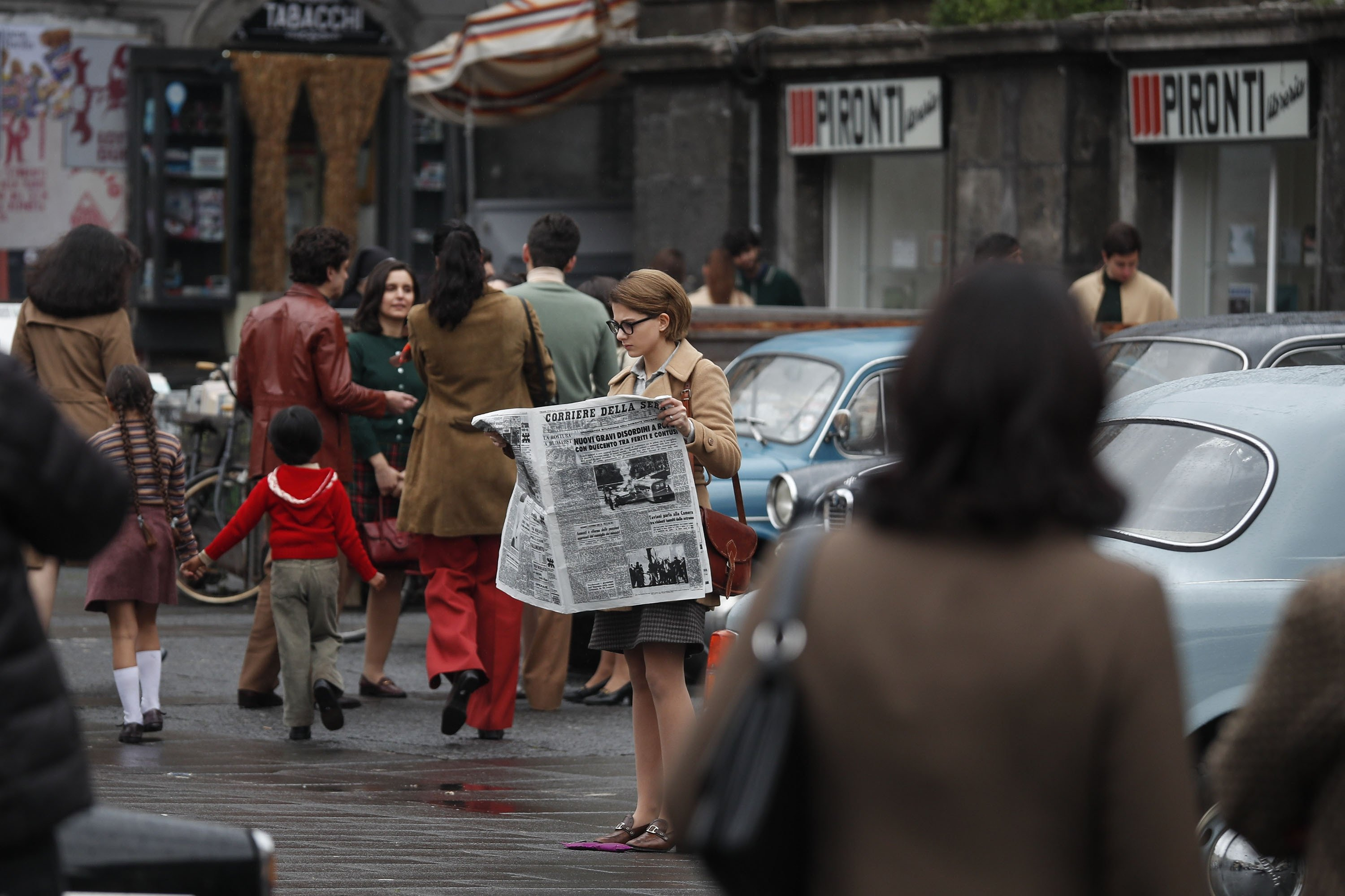 ActressMargherita Mazzucco (C) reads a newspaper on the streeton the set of the TV series 'My Brilliant Friend' ('L'amica geniale') based on the novels of Elena Ferrante, in Naples, Italy, Jan. 13, 2021. (Getty Images)