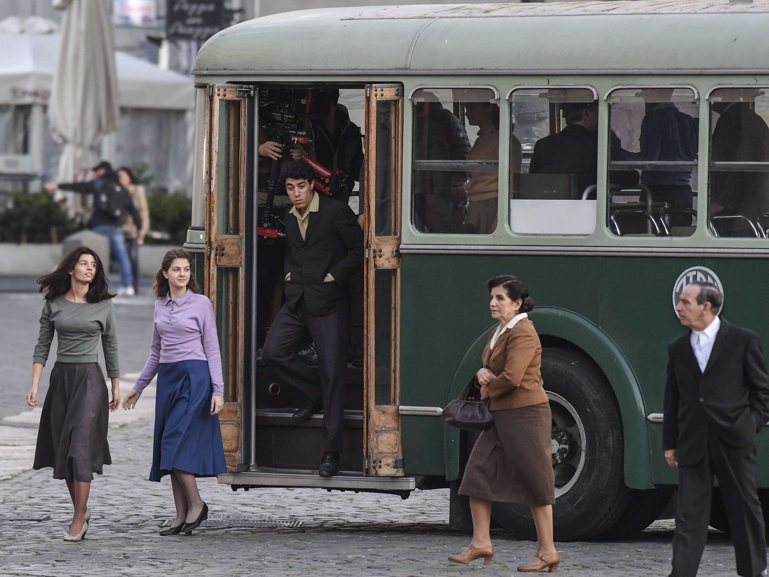 Gaia Girace (L) andMargherita Mazzucco (C-L) get off the buson the set of the TV series 'My Brilliant Friend' ('L'amica geniale') based on the novels of Elena Ferrante, in Naples, Italy, Jan. 13, 2021. (Getty Images)