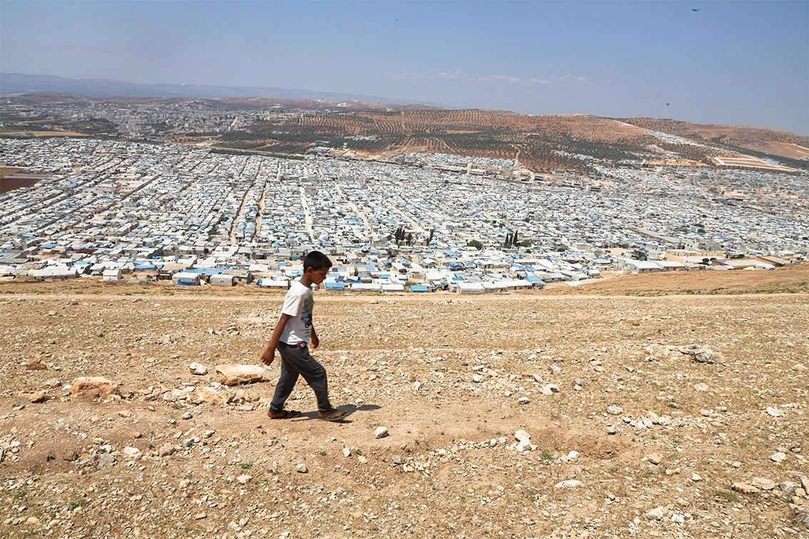 A displaced Syrian boy walks near the Karama camps in the northern countryside of Idlib governorate on the Syrian-Turkish border, May 30, 2021. (Getty Images)