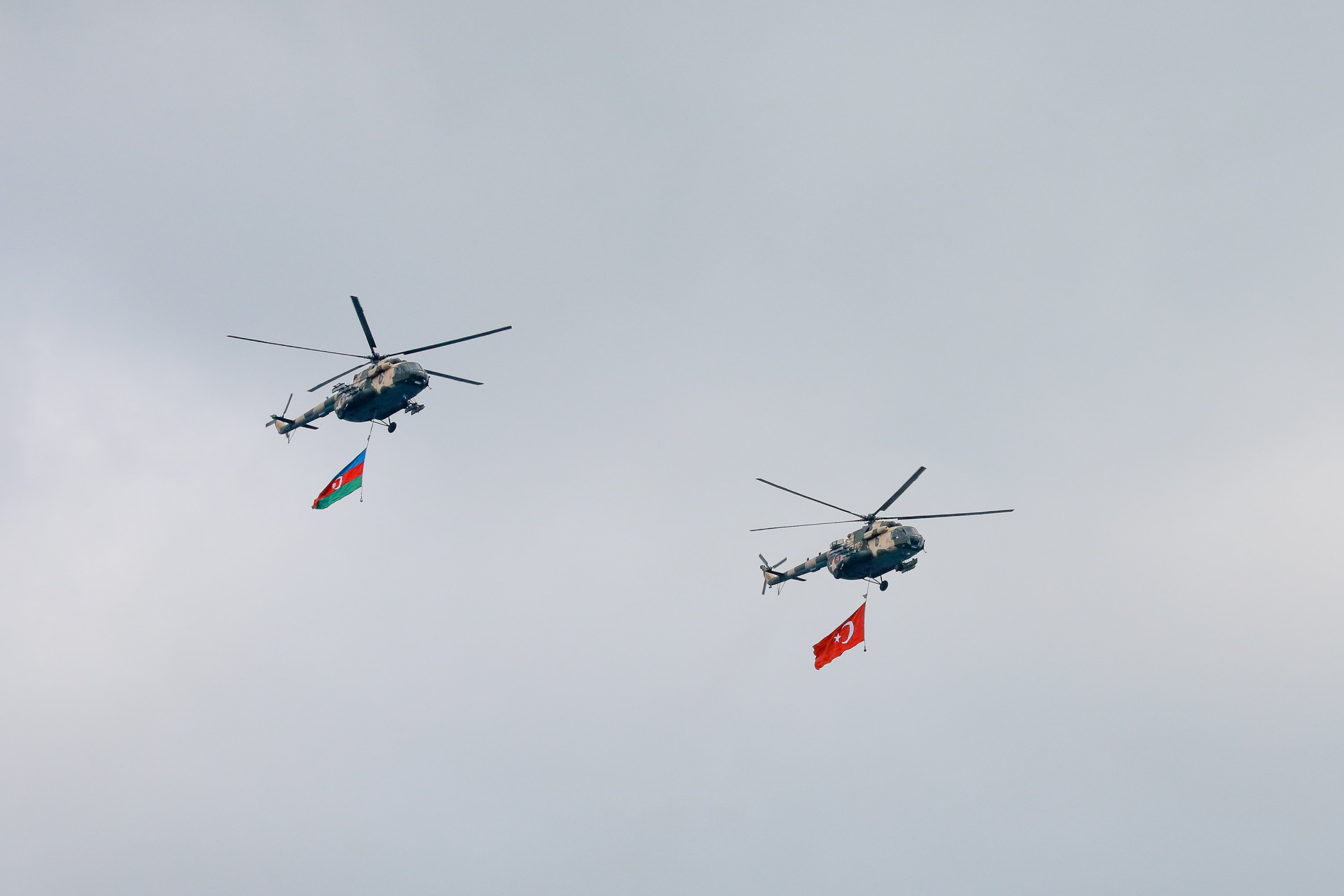 Mil Mi-17 military transport helicopters with the flags of Azerbaijan (L) and Turkey (R) are seen in flight during a military parade marking the end of the Nagorno-Karabakh military conflict, Baku, Azerbaijan, Dec. 10, 2020. (Photo by Getty Images)