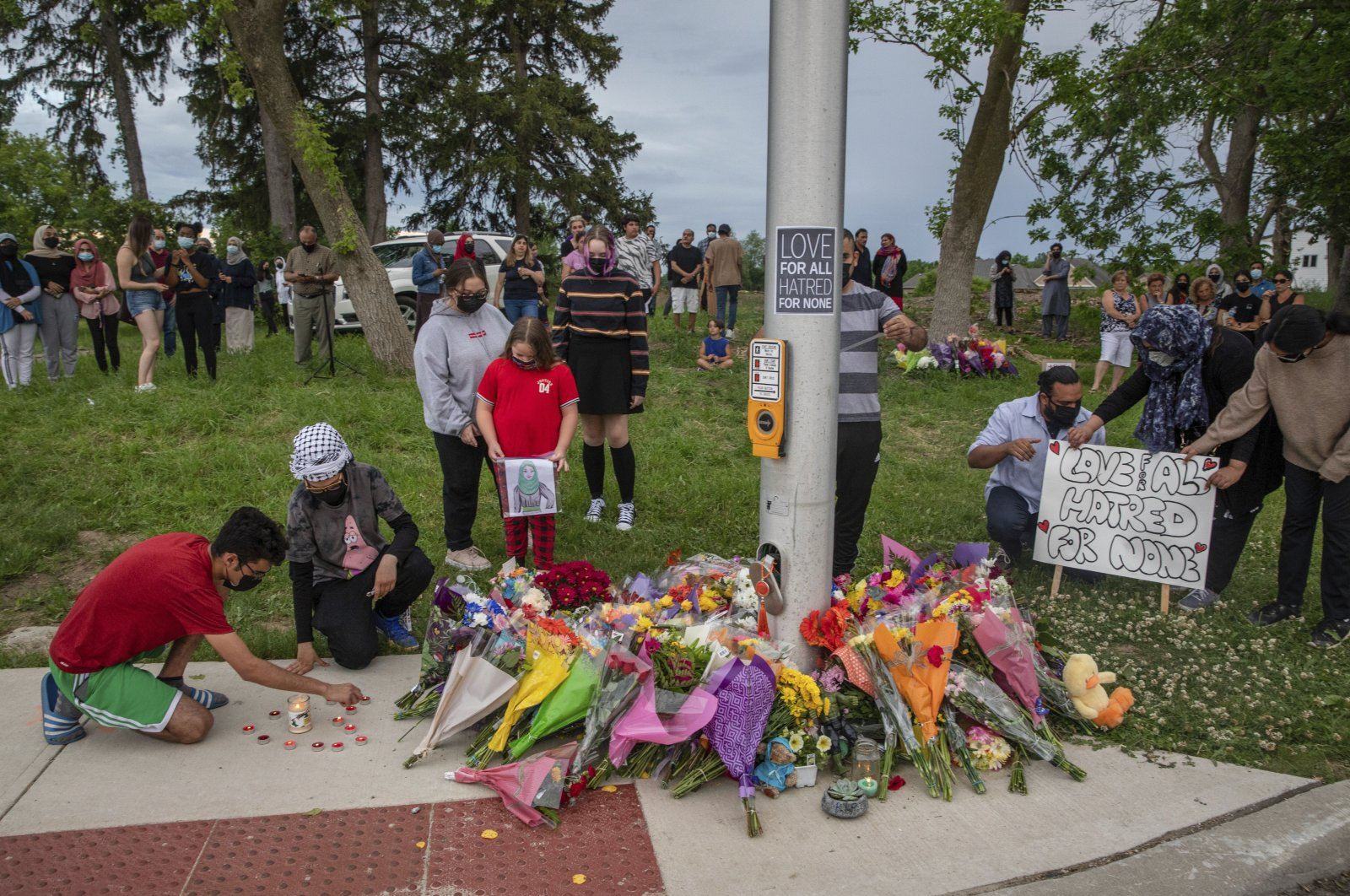People attend a memorial at the location where a family of five was hit by a driver, in London, Ontario, Canada, Monday, June 7, 2021. (AP Photo)