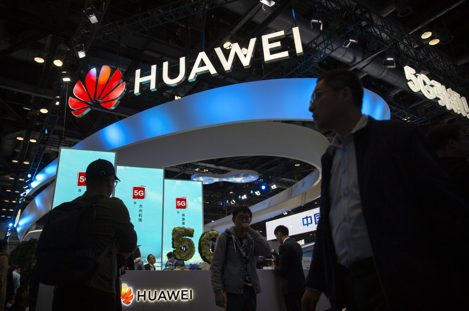 Attendees walk past a display for 5G services from Chinese technology firm Huawei at the PT Expo in Beijing, China, Oct. 31, 2019. (AP Photo)