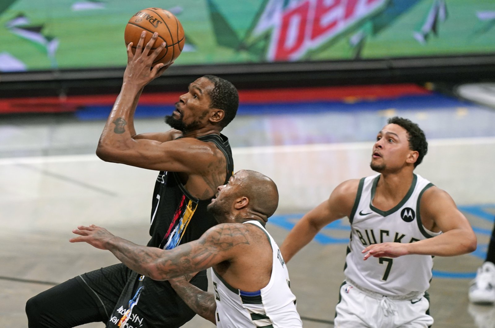 Brooklyn Nets forward Kevin Durant (L) goes up to shoot as Milwaukee Bucks forward P.J. Tucker (C) and guard Bryn Forbes (R) look on during Game 2 of their NBA second-round playoffs, June 7, 2021, New York, U.S. (AP Photo)