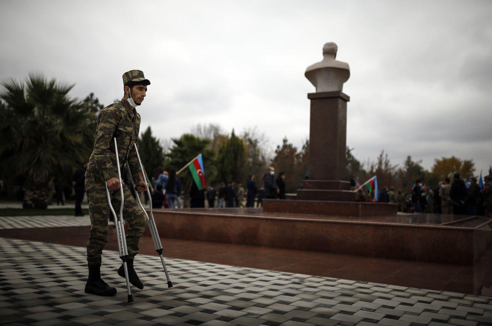 A wounded Azerbaijani soldier stands next to a bust of Azerbaijani President Ilham Aliyev's father and former Azerbaijani President Heydar Aliyev, in Aghjabadi, Azerbaijan, Tuesday, Dec. 1, 2020. (AP File Photo)