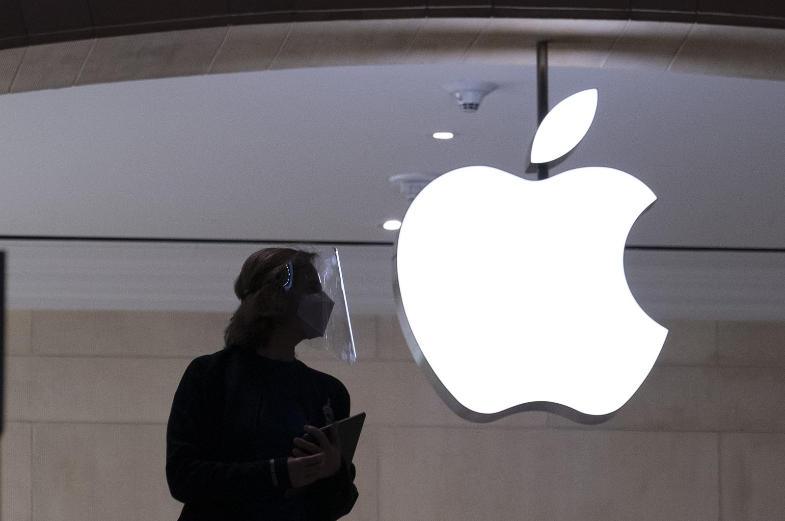 An Apple store employee wears personal protective equipment in New York, Feb. 5, 2021. (AP Photo)