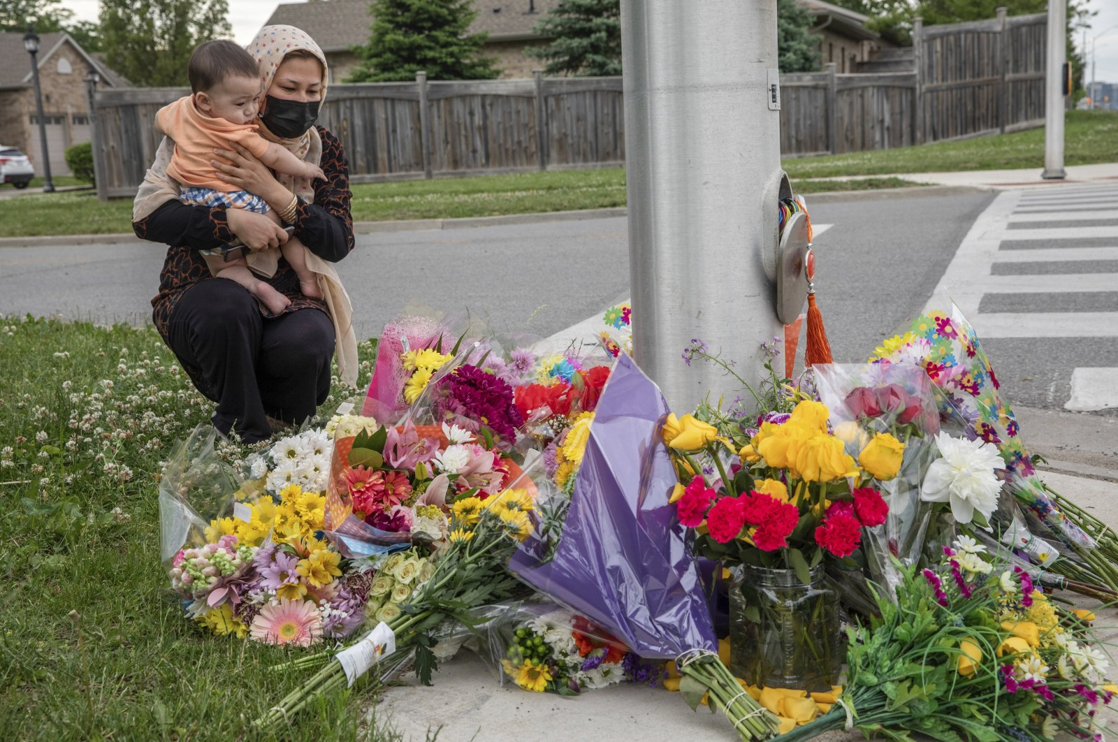 Nafisa Azima and her daughter Seena Safdari attend a memorial at the location where a family of five was hit by a driver, in London, Ontario, Monday, June 7, 2021. (AP Photo)