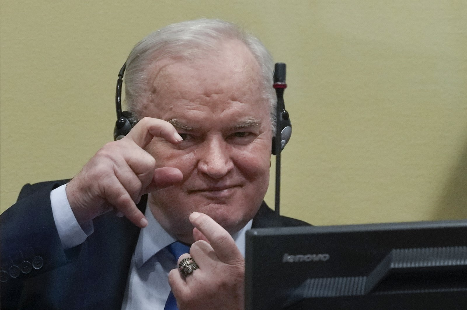 Former Bosnian Serb military chief Ratko Mladic imitates taking pictures as he sits in the court room in The Hague, Netherlands, June 8, 2021. (AP Photo)