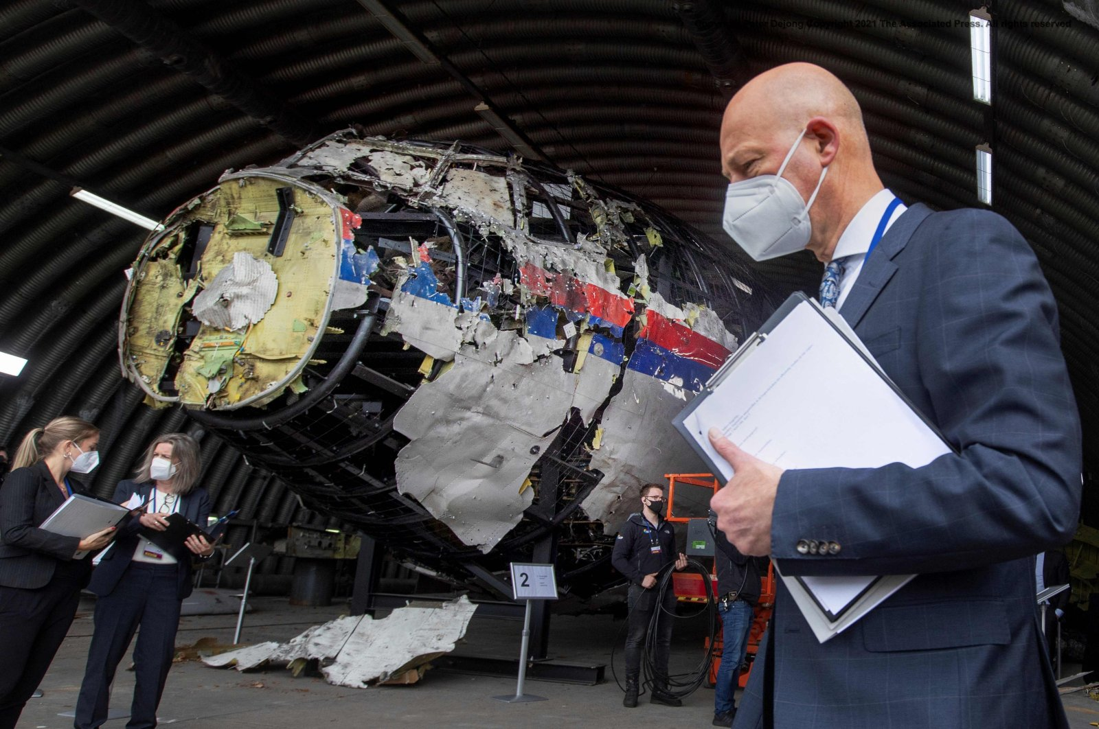 Judge Hendrik Steenhuis (C), other trial judges and lawyers view the reconstructed wreckage of Malaysia Airlines flight MH17, at the Gilze-Rijen military air base, near Breda, Netherlands, May 26, 2021. (AFP Photo)