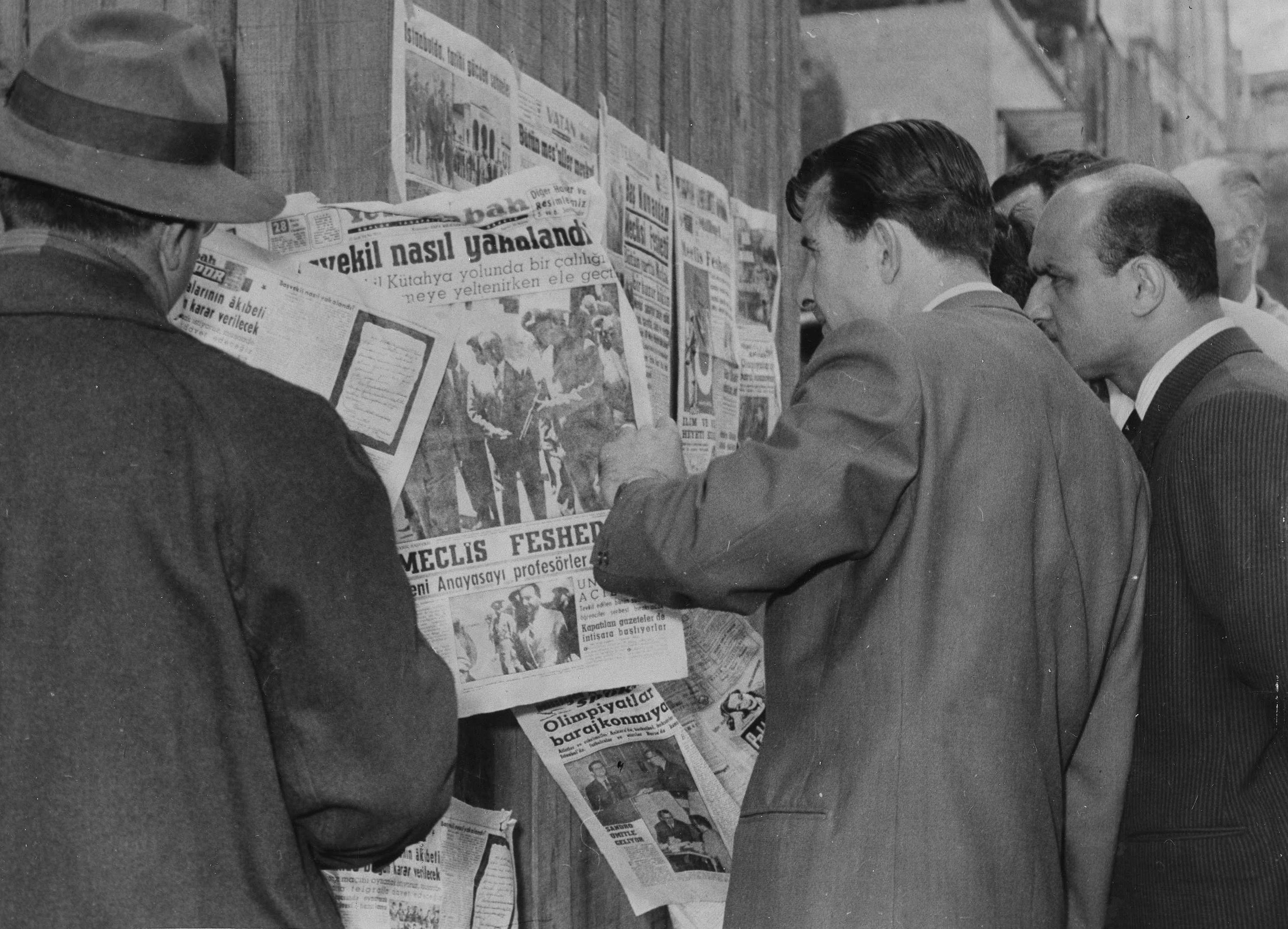 Citizens stand near a newsstand featuring newspapers announcing the arrest of Prime Minister Adnan Menderes after a military coup, in Istanbul, Turkey, May 28, 1960. (AP Photo)