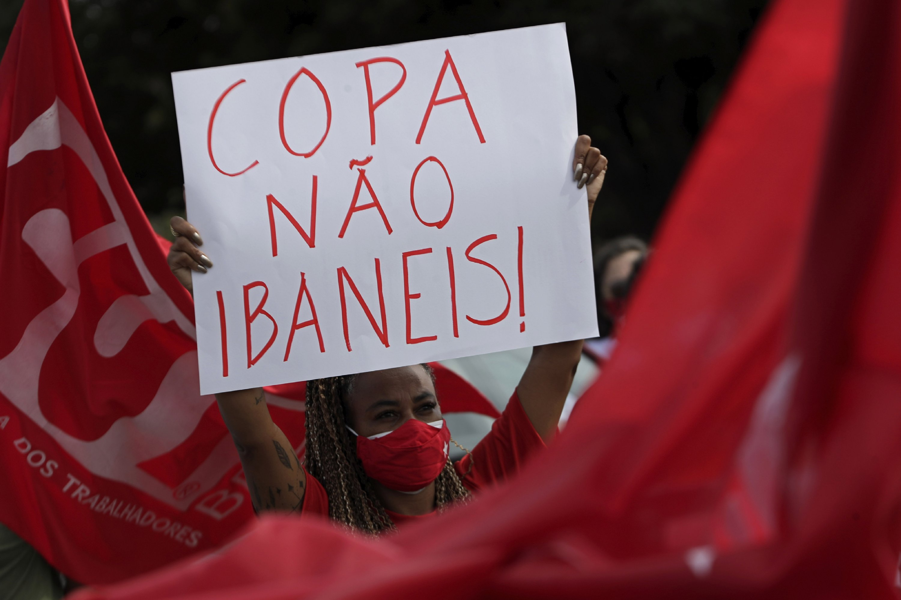 A woman holds a sign to protest Brazil's decision to hold the Copa America in Brasilia, Brazil, June 6, 2021. (AP Photo)