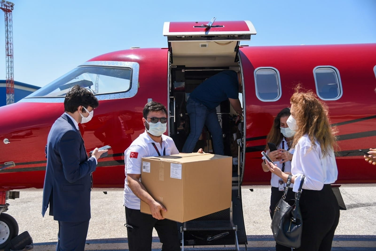 People unload boxes of vaccines from an airplane in an unknown location in North Macedonia in a photo shared by the country's Health Minister on his Facebook account, North Macedonia, June 9, 2021. (AA PHOTO)