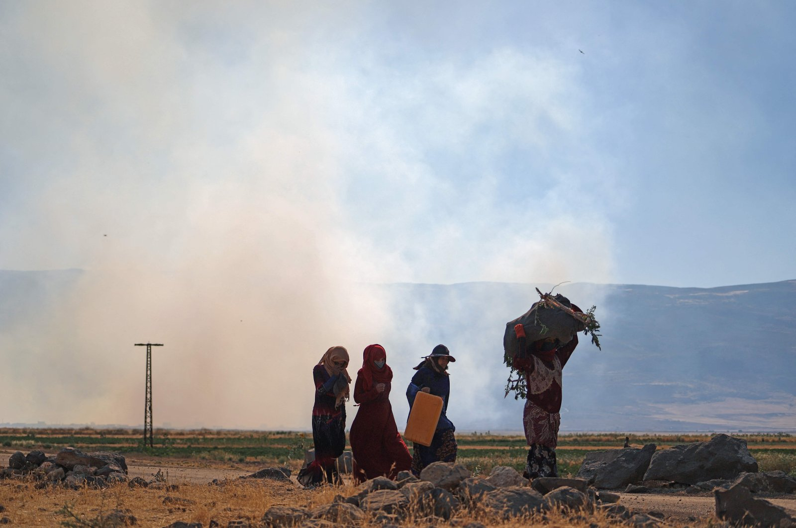 Syrian women walk by billowing smoke following a reported pro-Assad regime bombardment, near the village of al-Ziyarah in the agricultural al-Ghab plain of Hama province, Syria, June 6, 2021. (AFP Photo)