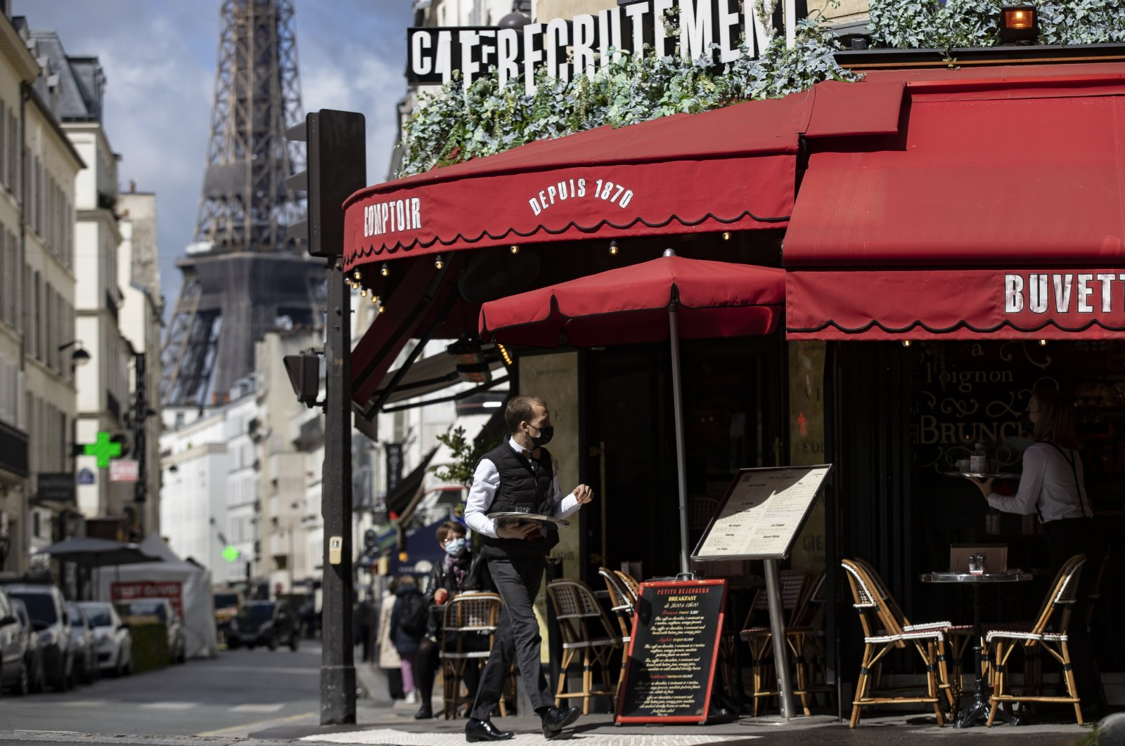 A waiter serves beverages on a cafe's terrace near the Eiffel Tower during the reopening of restaurant terraces and bars, Paris, France, May 19, 2021. (EPA-EFE Photo)