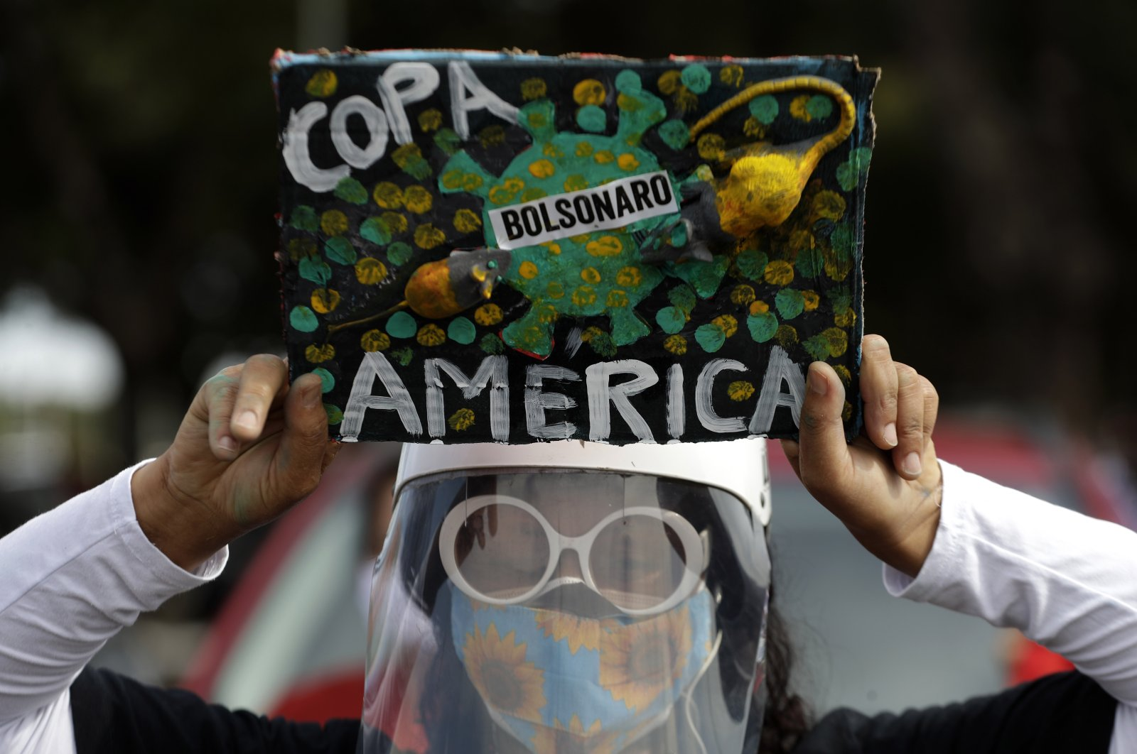 A woman holds a sign to protest against Brazil holding the Copa America in Brasilia, Brazil, Sunday, June 6, 2021. (AP Photo)