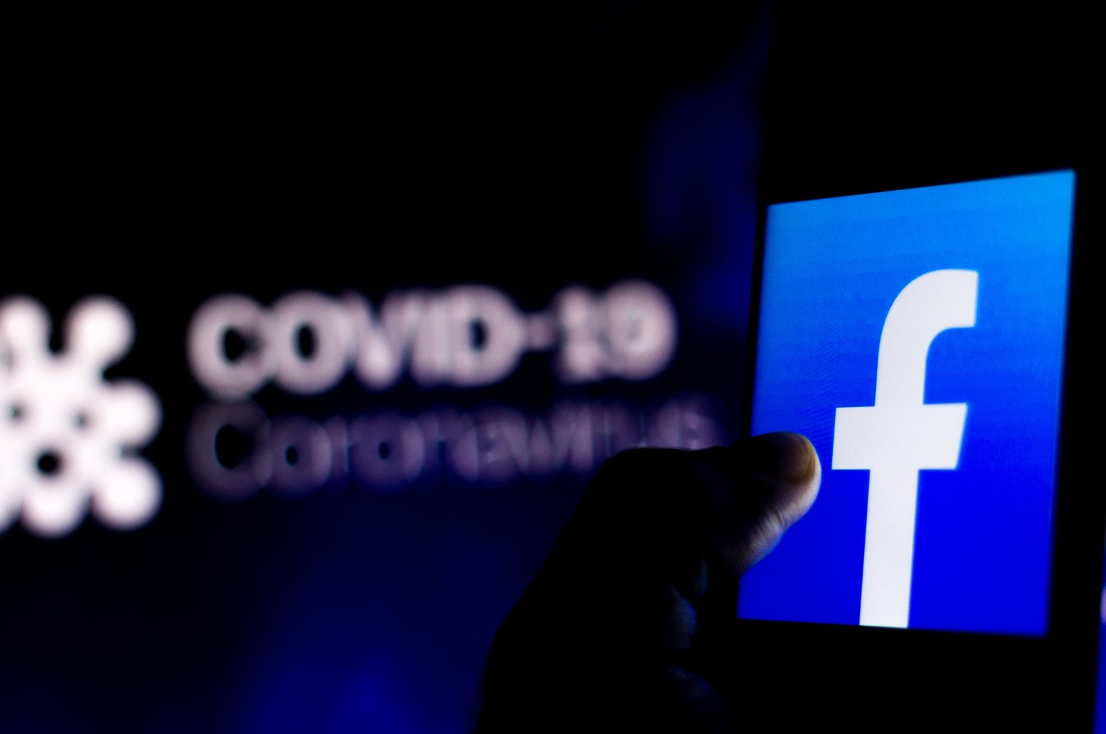 The Facebook logo is seen displayed on a smartphone with a computer model of the COVID-19 coronavirus in the background, April 5, 2020. (Photo by Shutterstock)