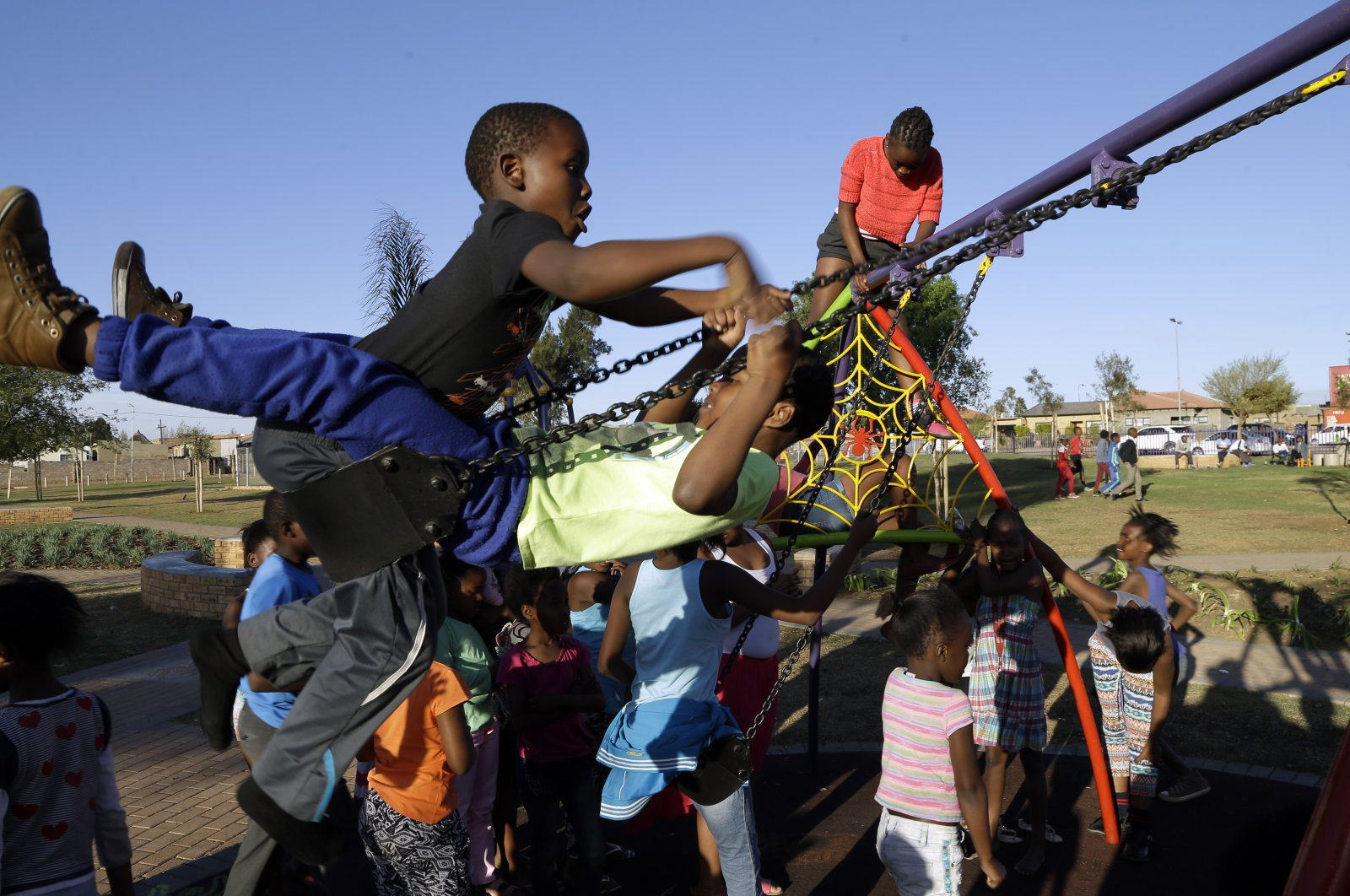 Children play on a swing at the newly built Meadowlands Park in Soweto, South Africa, Sept. 2, 2015. (AP Photo)