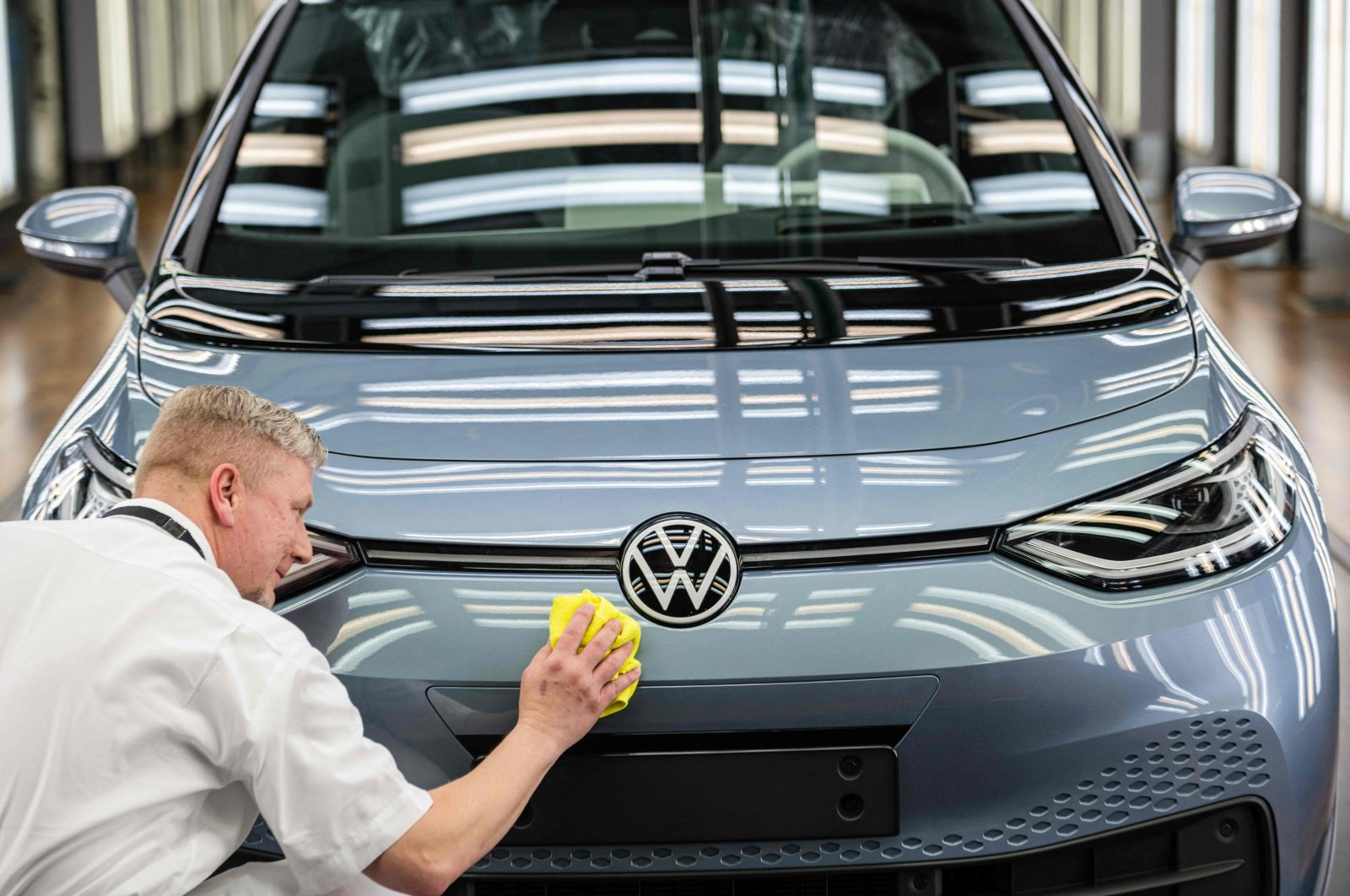 """An employee checks the surface of an """"ID 3"""" electric car of German carmaker Volkswagen, at the """"Glassy Manufactory"""" (Glaeserne Manufaktur) production site in Dresden, Germany, June 8, 2021. (AFP Photo)"""