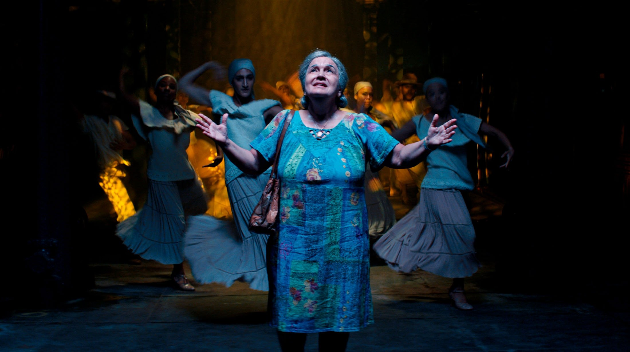 Actress Olga Merediz (C) opens her arms in a scene from the musical film 'In the Heights.' (Warner Bros. via AP)