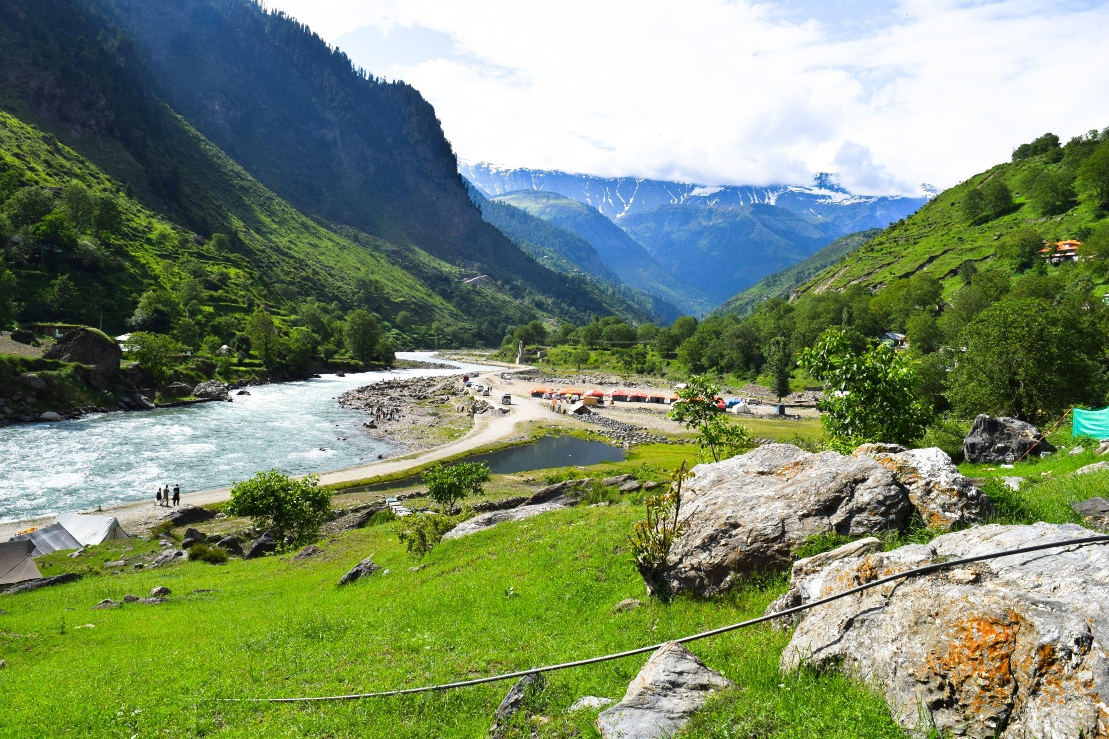 Water flows through the Kaghan Valley covered with pine forests with the Himalayan mountain range in the background, Pakistan. (Shutterstock Photo)