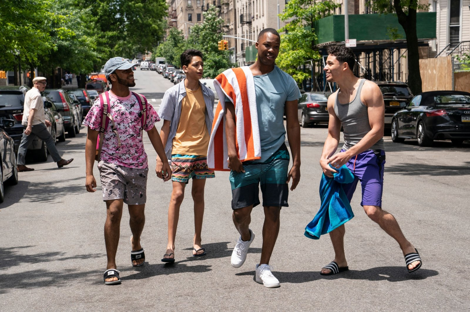 """Noah Catala (L), Gregory Diaz IV (C-L), Corey Hawkins (C-R) and Anthony Ramos walk togetheron the road in a scene fromthe musical movie """"In the Heights."""" (Warner Bros. via AP)"""