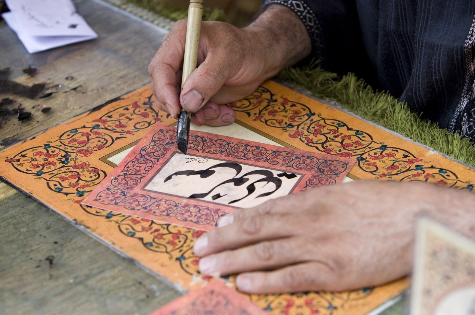 A man writes down a name in traditional Arabic characters in calligraphy. (Shutterstock Photo)