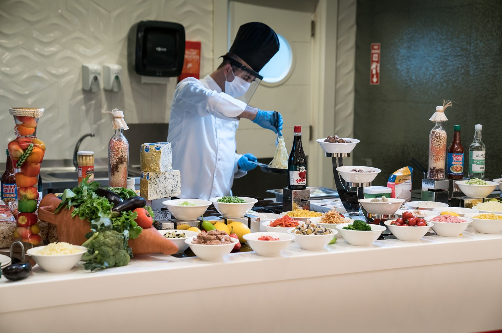 A chef wearing protective gear against the COVID-19 pandemic presents food in an open buffet food service in a restaurant in Antalya, southern Turkey, June 22, 2020. (Shutterstock Photo)