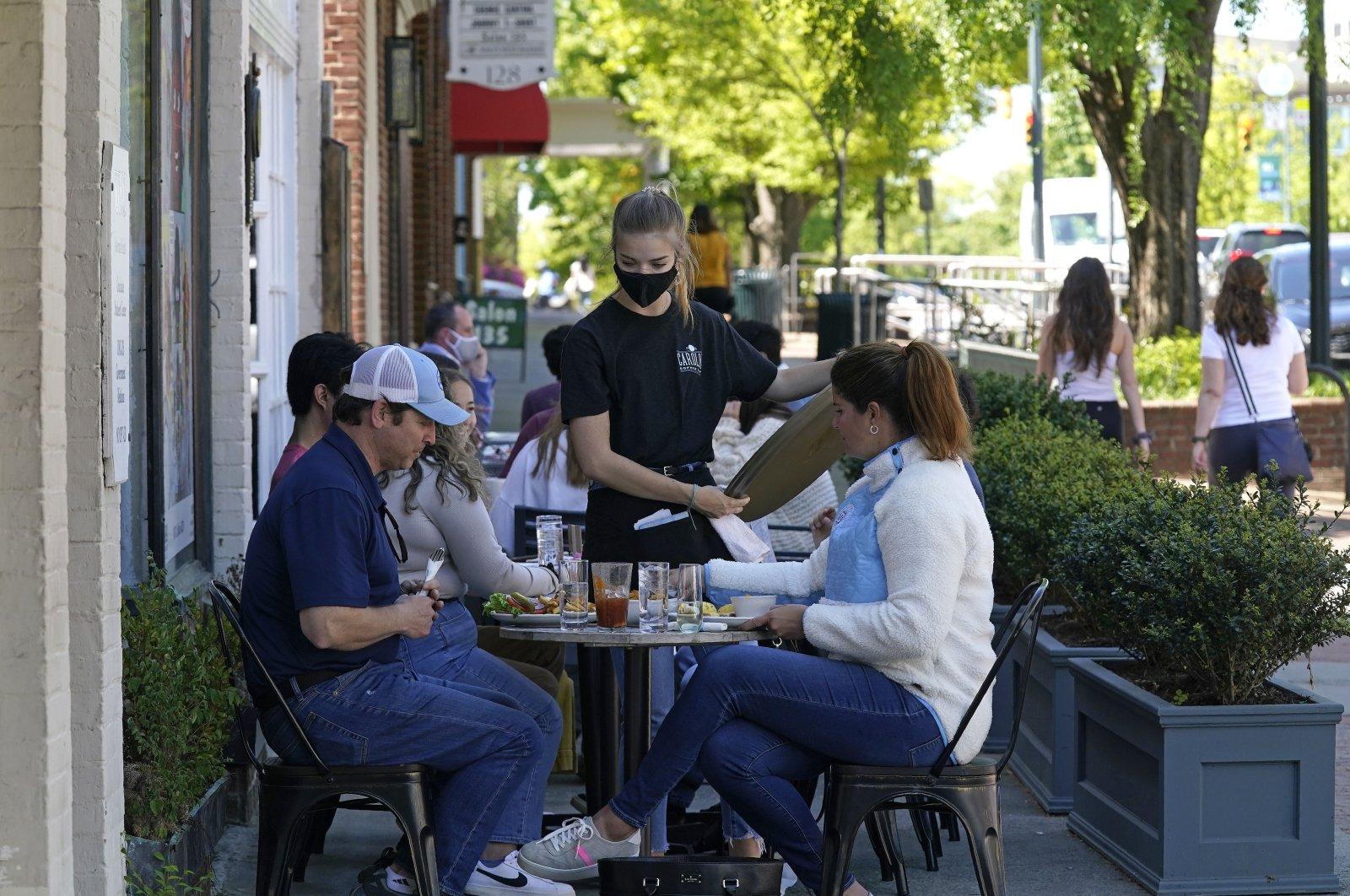 People dine along a sidewalk on Franklin Street in Chapel Hill, North Carolina, U.S., April 16, 2021. (AP Photo)
