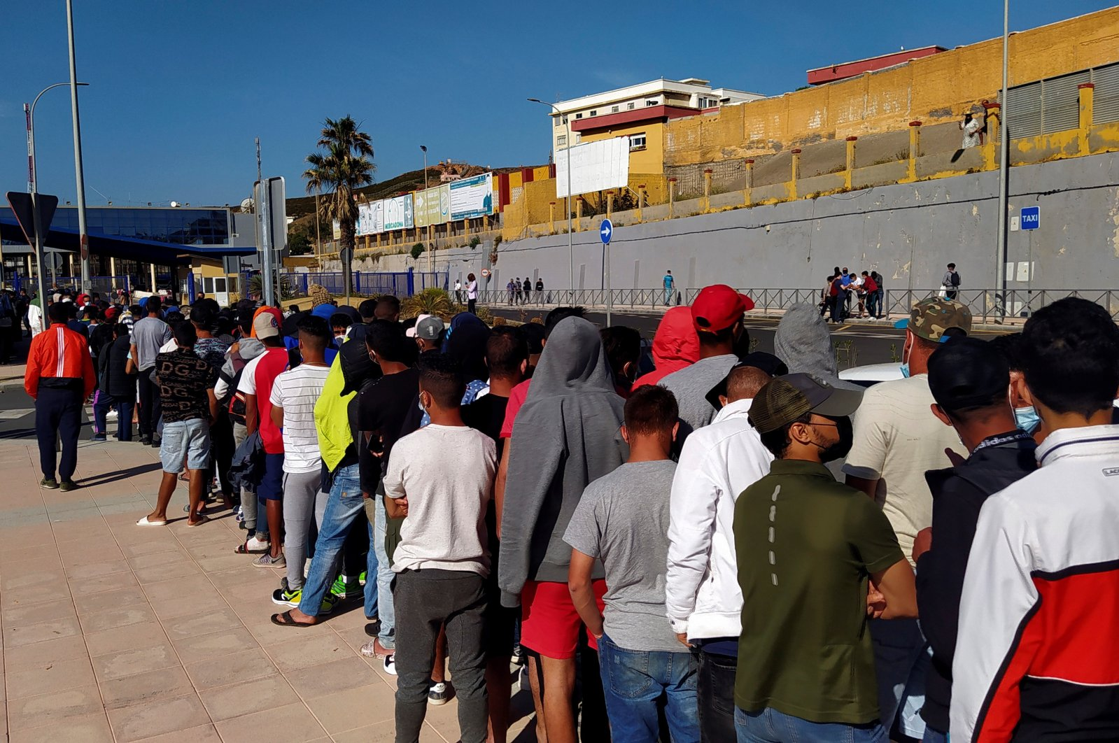Moroccan migrants wait in a long line in front of Asylum and Refuge Office at Tarajal border crossing in Ceuta, Spanish enclave in northern Africa, June 2, 2021.  (EPA/Reduan Dris)