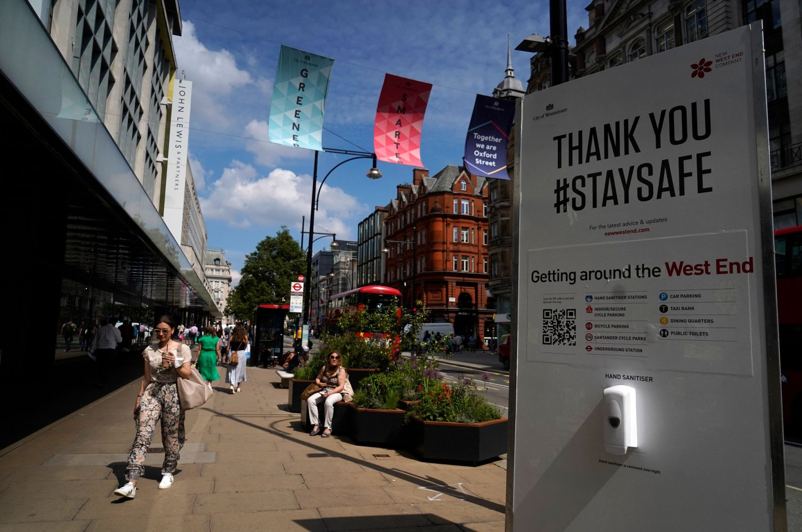 Pedestrians, some wearing face coverings due to COVID-19, walk past a coronavirus information sign as they pass shops on Oxford Street in central London on June 7, 2021. (AFP Photo)