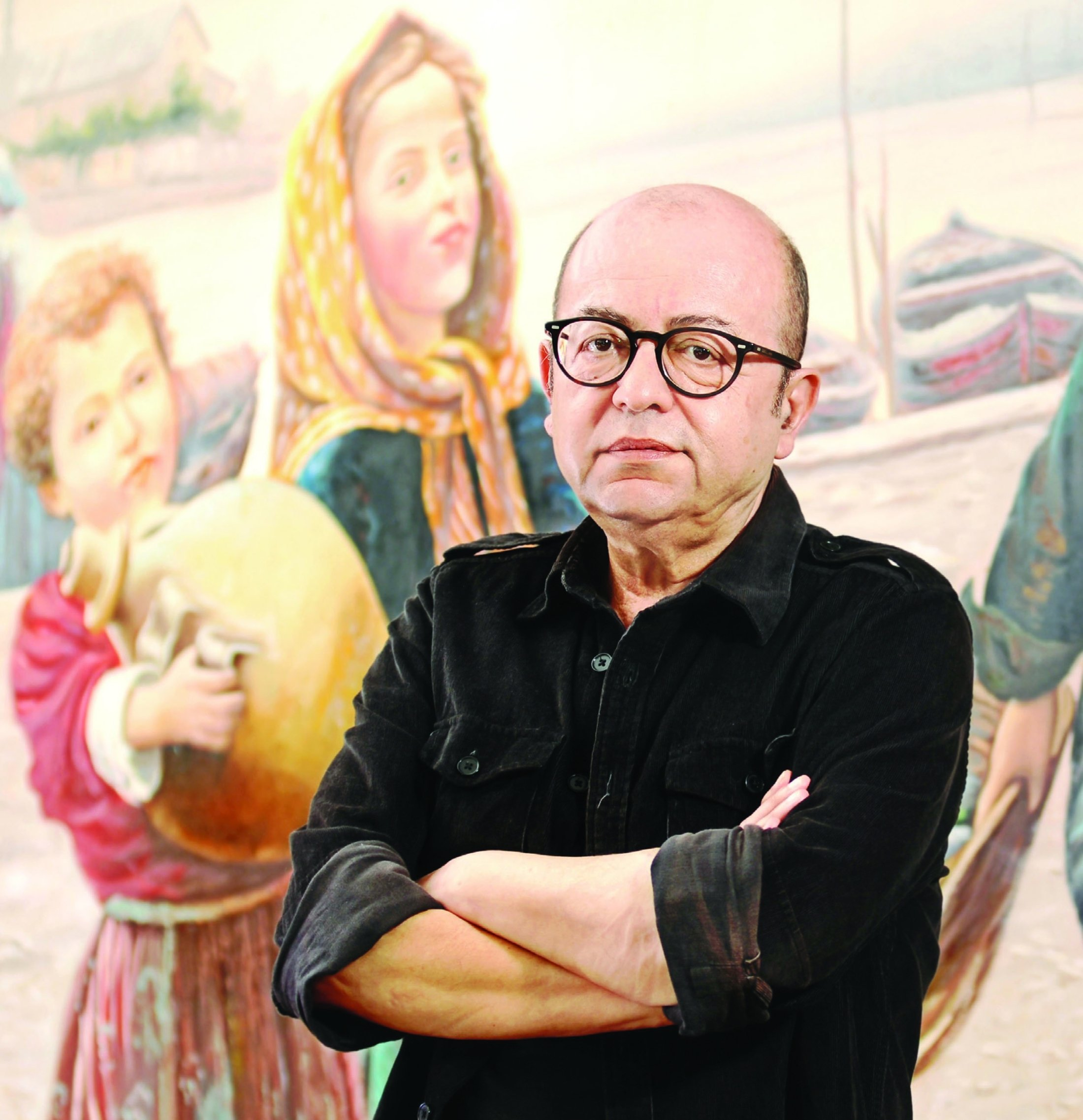 Author Selim Ileri poses for a photo with a mural in the background, Istanbul, Turkey, Aug. 23, 2013. (Archive Photo)
