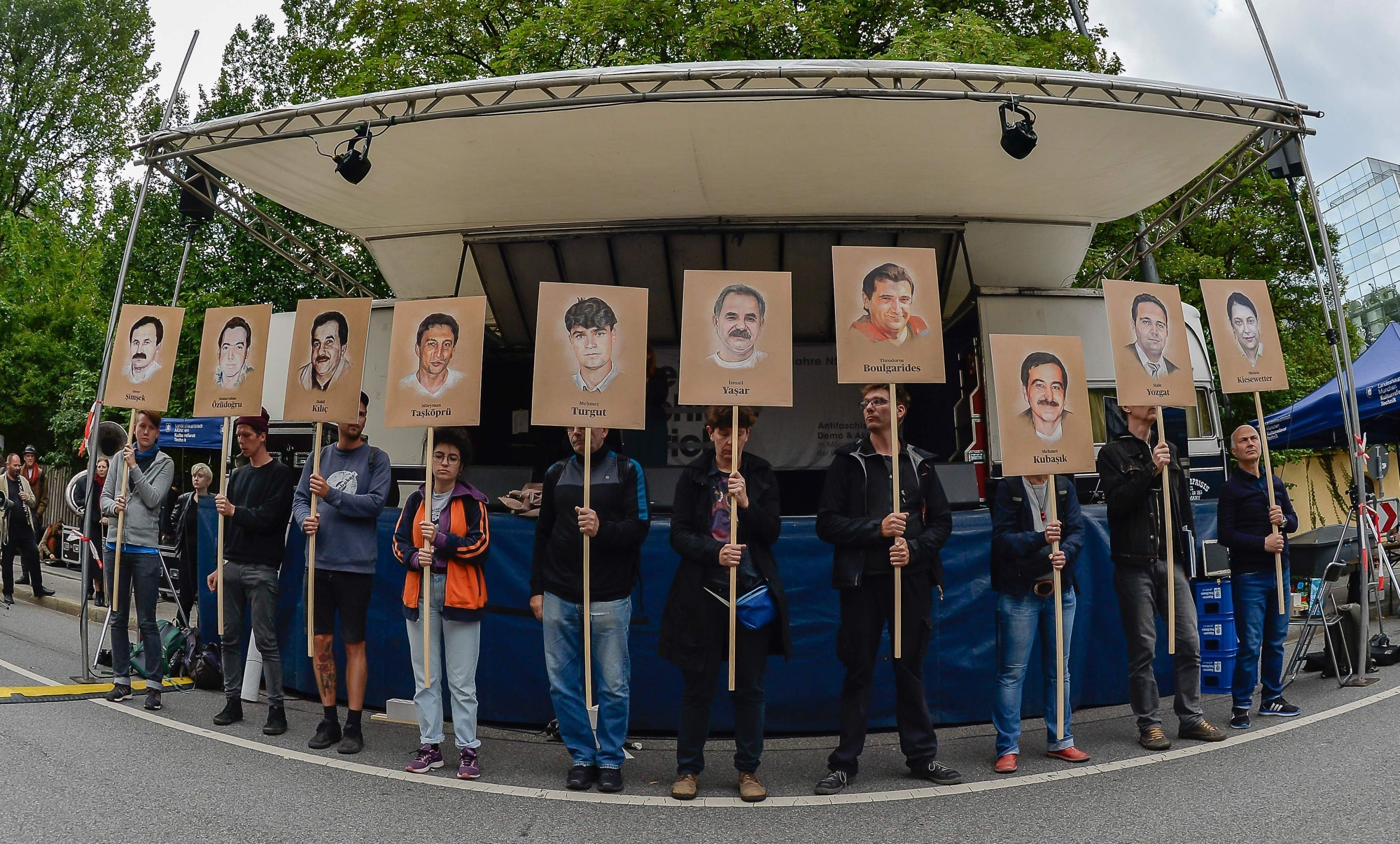 Protesters hold up signs with pictures of the victims of the neo-Nazi cell National Socialist Underground (NSU) before the proclamation of a sentence in the trial against Beate Zschaepe, the only surviving member of the NSU, which was behind a string of racist murders, in Munich, Germany, July 11, 2018. (AFP Photo)
