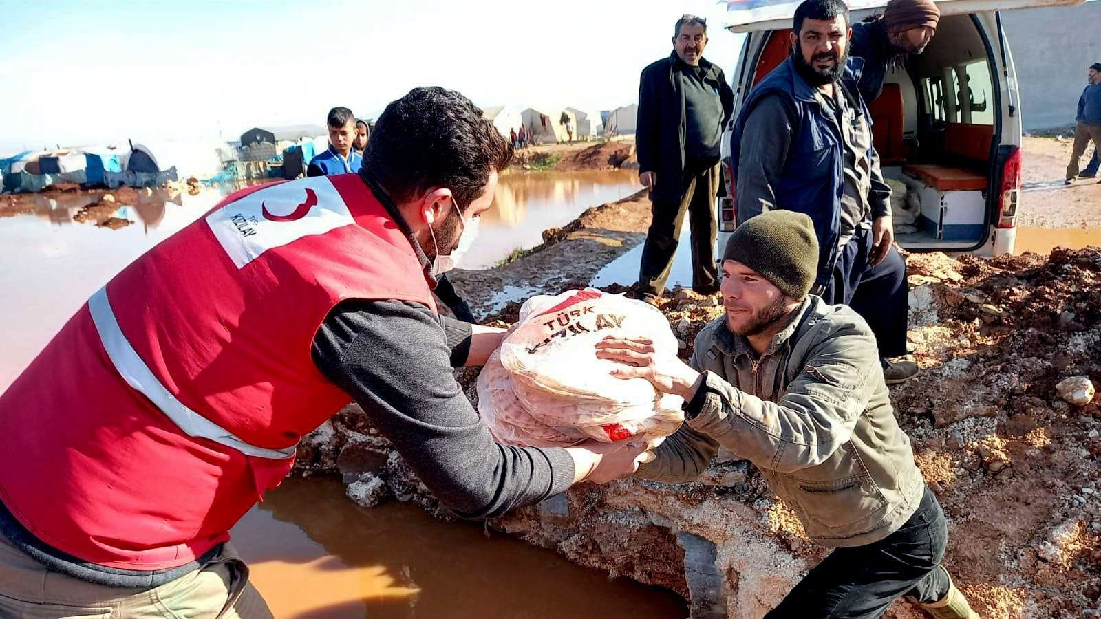 A Turkish Red Crescent worker hands over food to Syrians affected by floods in Idlib, Syria, Jan. 21, 2021. (AA PHOTO)