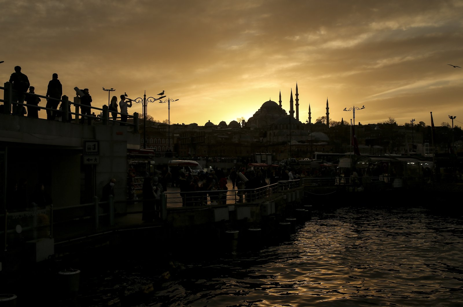 People meander on a bridge amid the coronavirus outbreak, in Istanbul, Turkey, Feb. 11, 2021. (AP Photo)