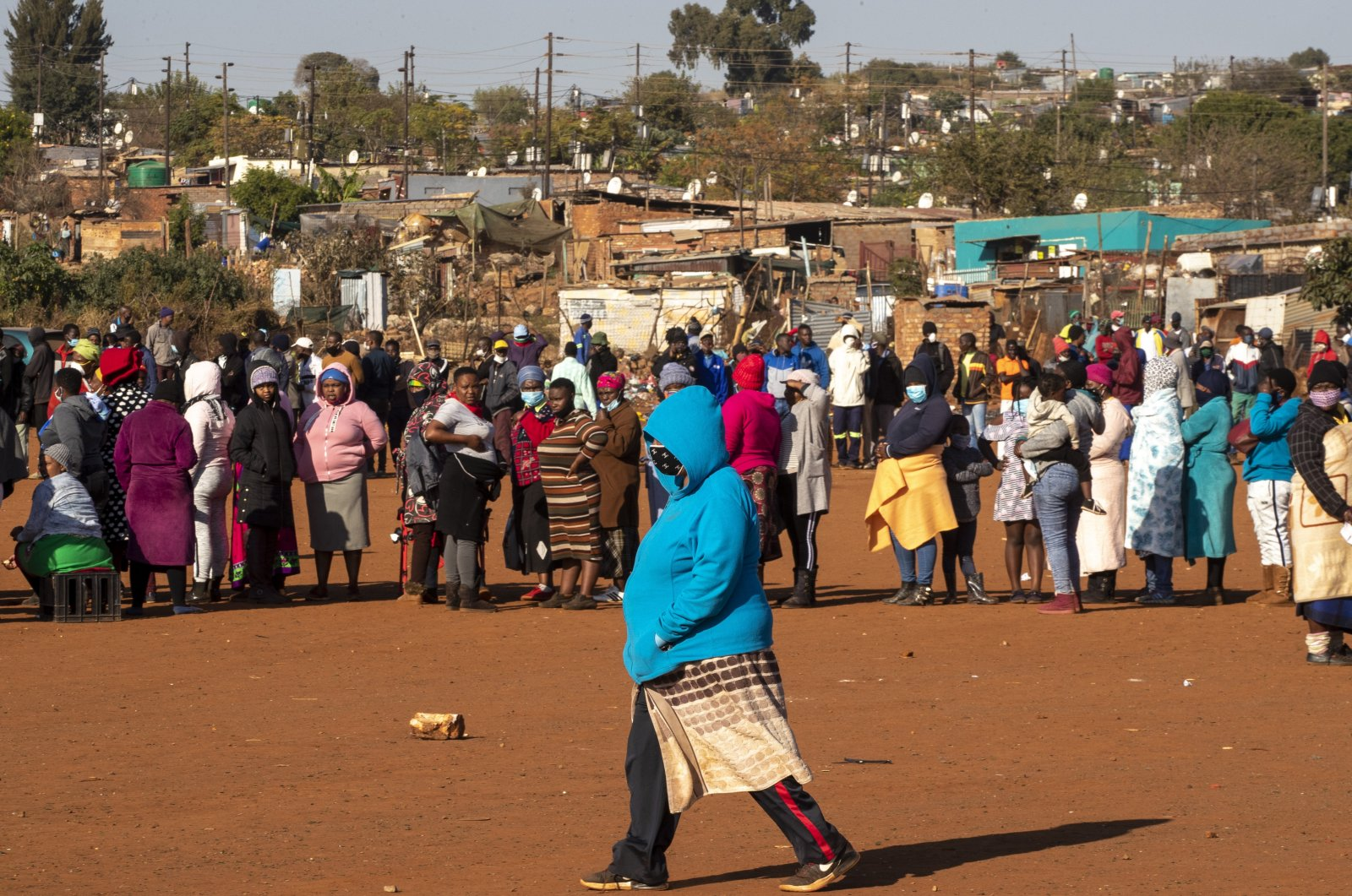 A woman walks across a dusty soccer field as people affected by the coronavirus economic downturn line up to receive food donations at the Iterileng informal settlement near Laudium, southwest of Pretoria, South Africa, May 20, 2020. (AP Photo)