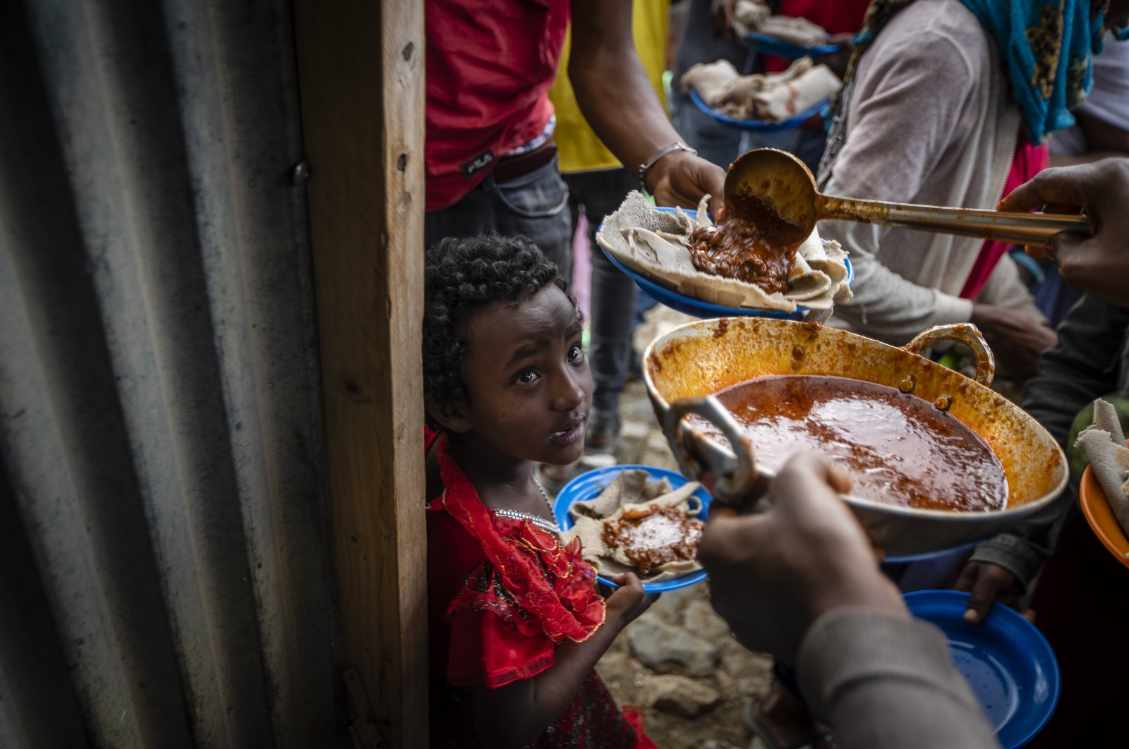 Elena, 7, (C) lines up with other displaced Tigrayans to receive food donated by local residents at a reception center for the internally displaced in Mekele, in the Tigray region of northern Ethiopia, May 9, 2021. (AP Photo)