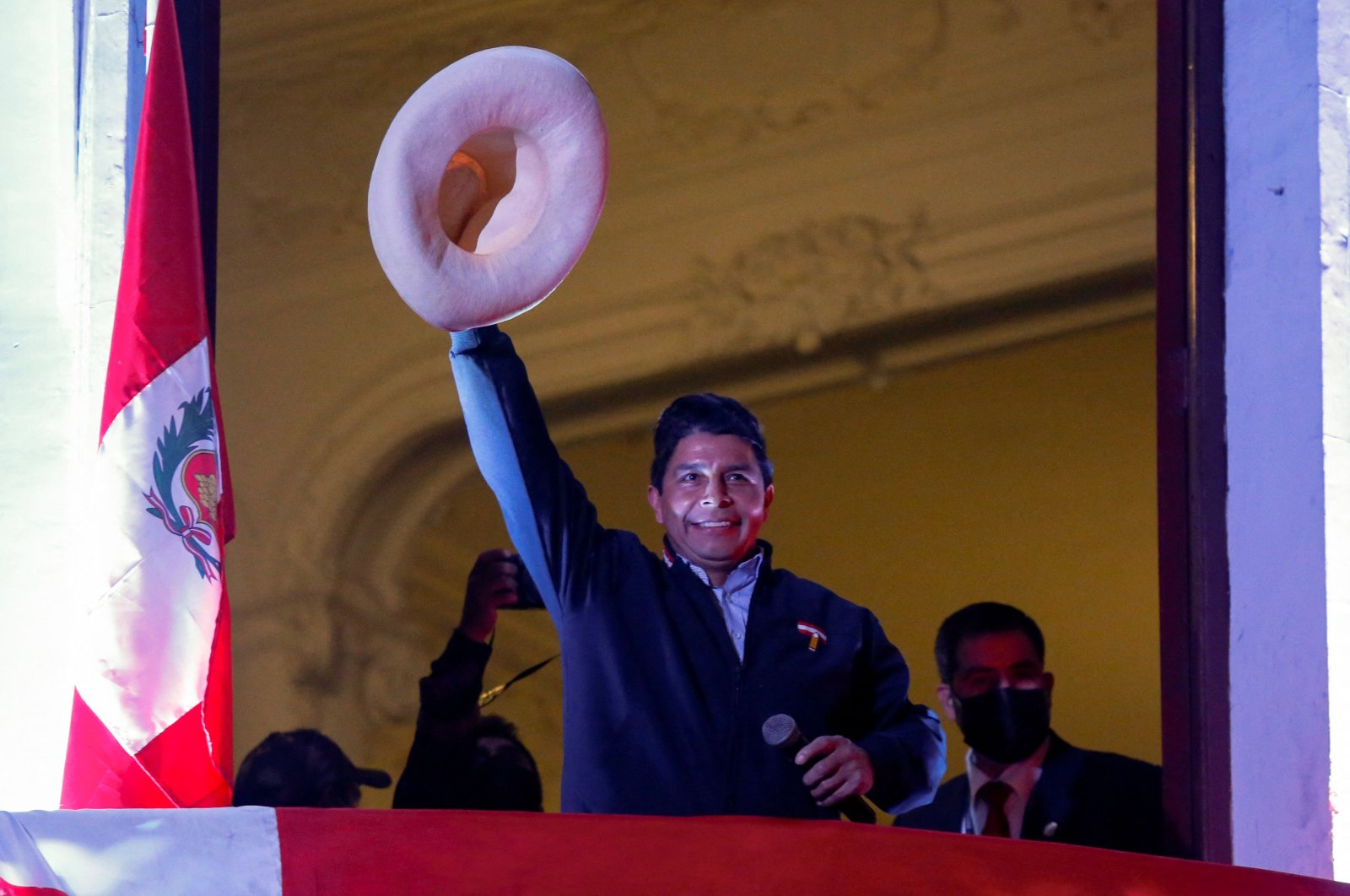 Peru's left-wing presidential candidate Pedro Castillo of the Peru Libre party, gestures to his supporters from the balcony of his party headquarters in Lima, Peru, June 10, 2021. (AFP Photo)
