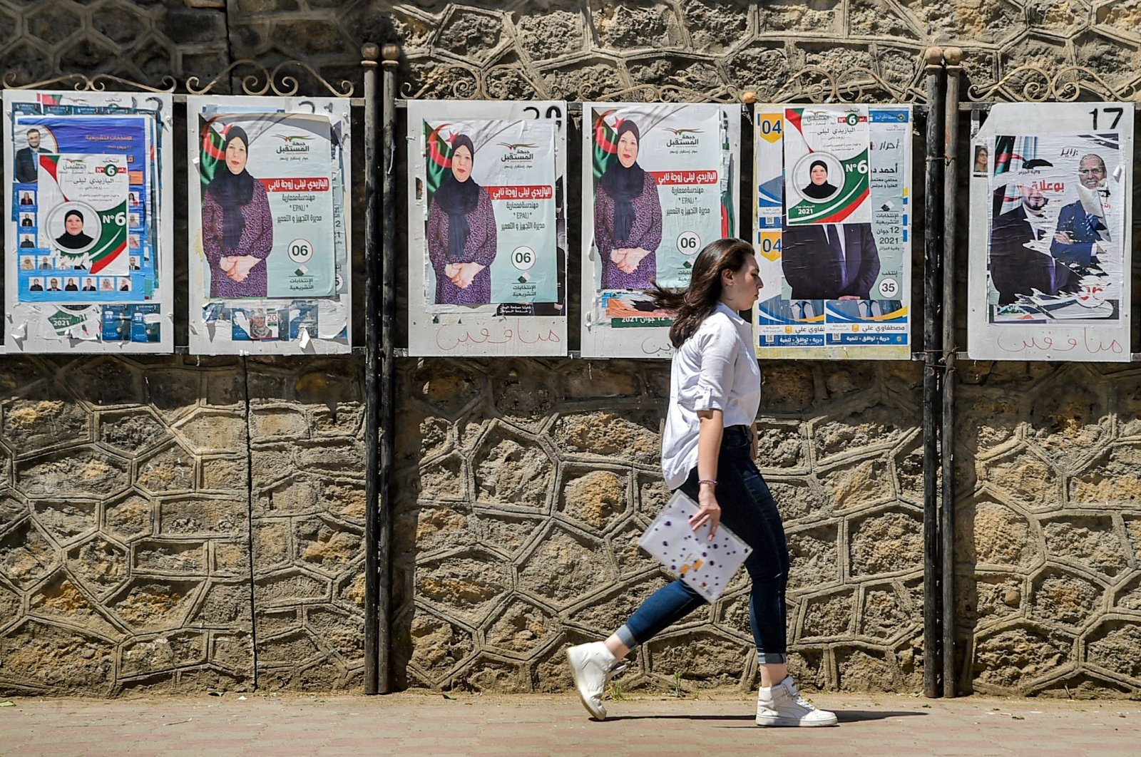 """A woman walks past a fence showing electoral posters of a candidate of the """"Future Front"""" political party in the Algerian capital, Algiers, June 11, 2021. (AFP Photo)"""