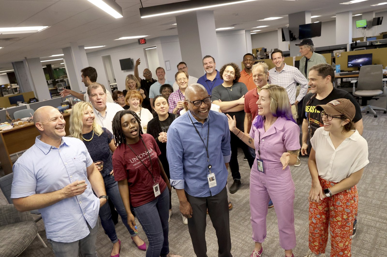 Michael Paul Williams (C), a columnist for the Richmond Times-Dispatch, celebrates with other newsroom staff at the newspaper Friday, June 11, 2021, in Richmond, Va. The Pulitzer Prize for commentary went to Williams for his series of columns on dismantling Confederate monuments in Richmond following Floyd's death. (AP Photo)