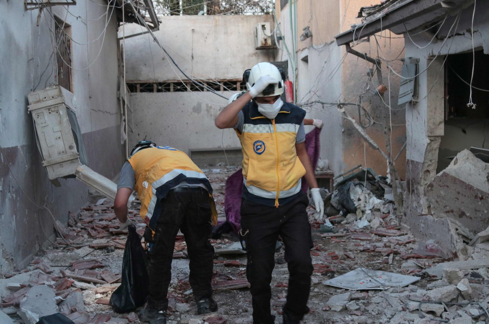 Members of Syria's Civil Defence (White Helmets) sift through the rubble at Al-Shifaa Hospital following the YPG shelling of the opposition-held city of Afrin in northern Syria, June 12, 2021. (AFP Photo)