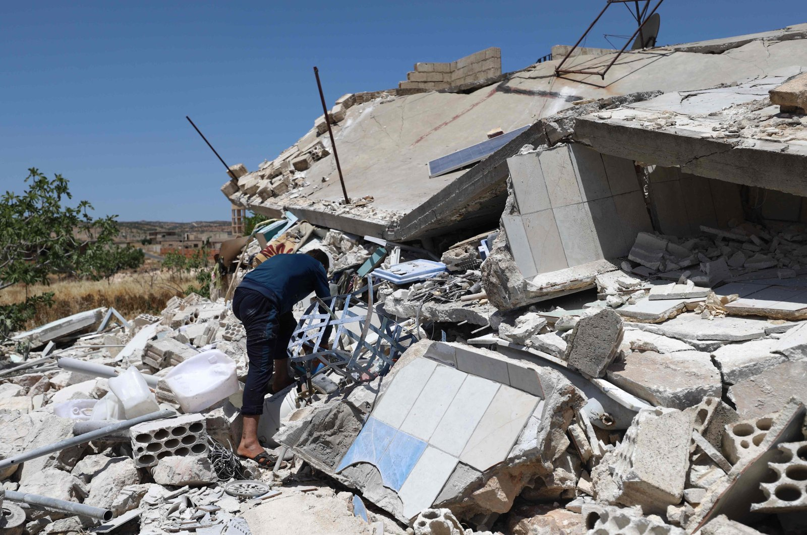 A man looks through the rubble of a destroyed house in the village of Iblin in the Jabal al-Zawiya region in northwestern Syria's Idlib province, June 10, 2021. (AFP Photo)