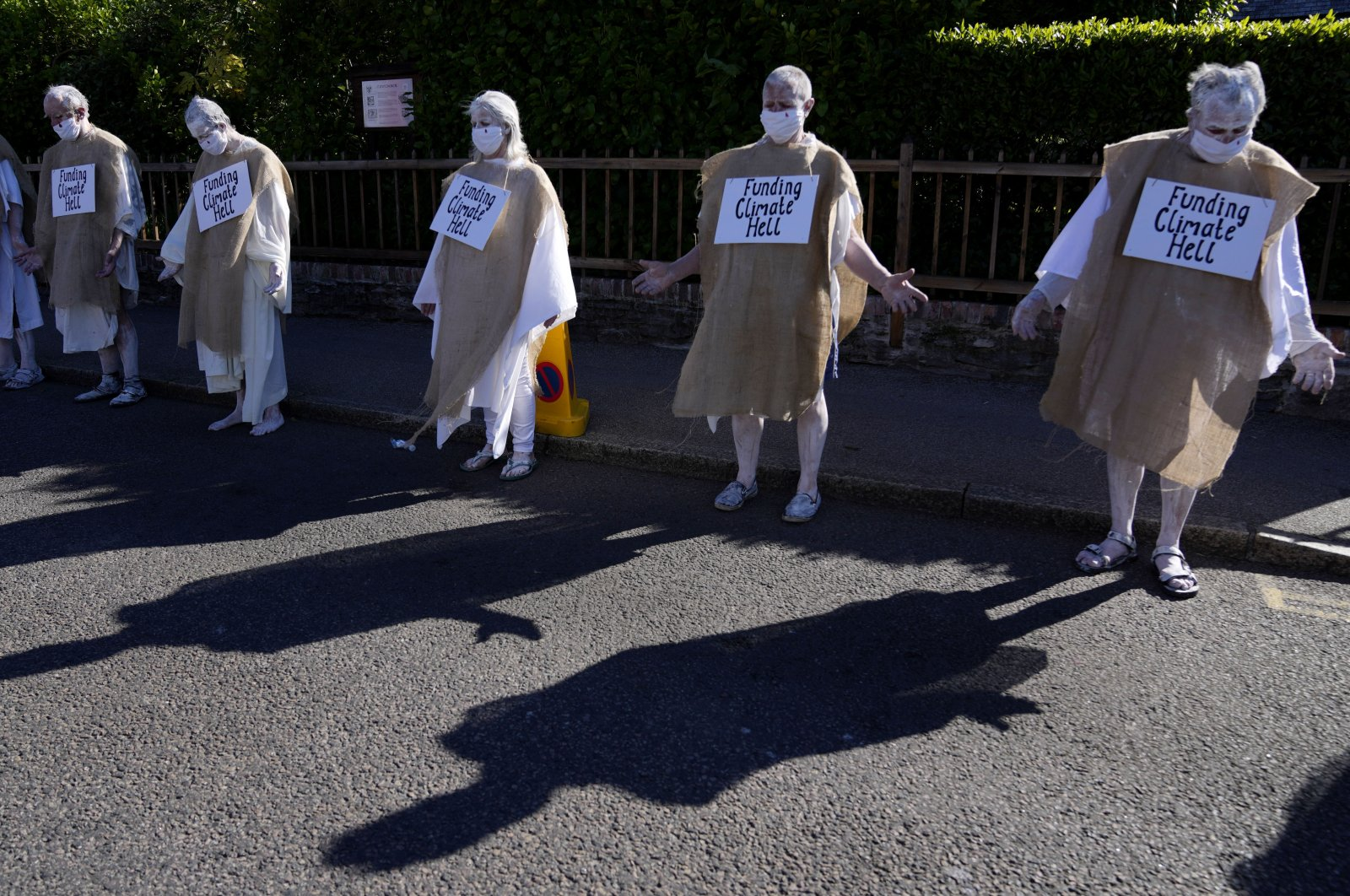 Climate protestors march in potato sacks with signs during a demonstration in Falmouth, Cornwall, England, June 12, 2021. (AP Photo)