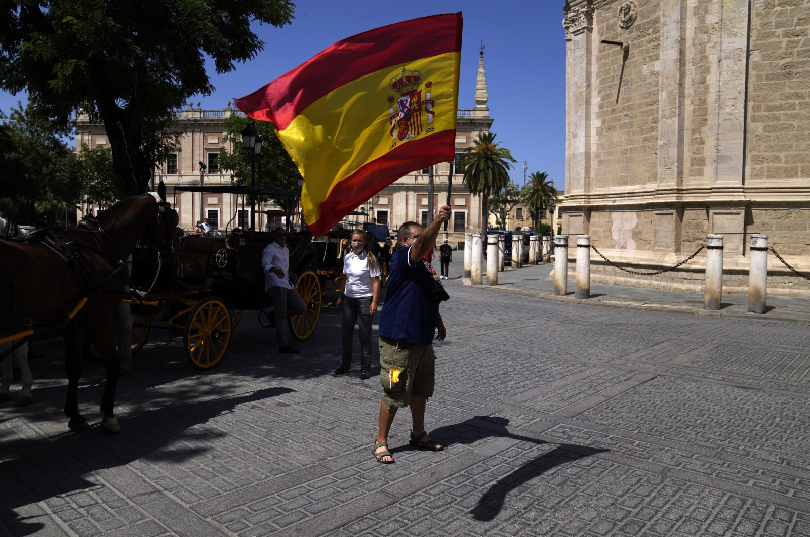 A Spanish fan waves his country's flag at Plaza del Triunfo in Seville, Spain, June 13, 2021. (AP Photo)