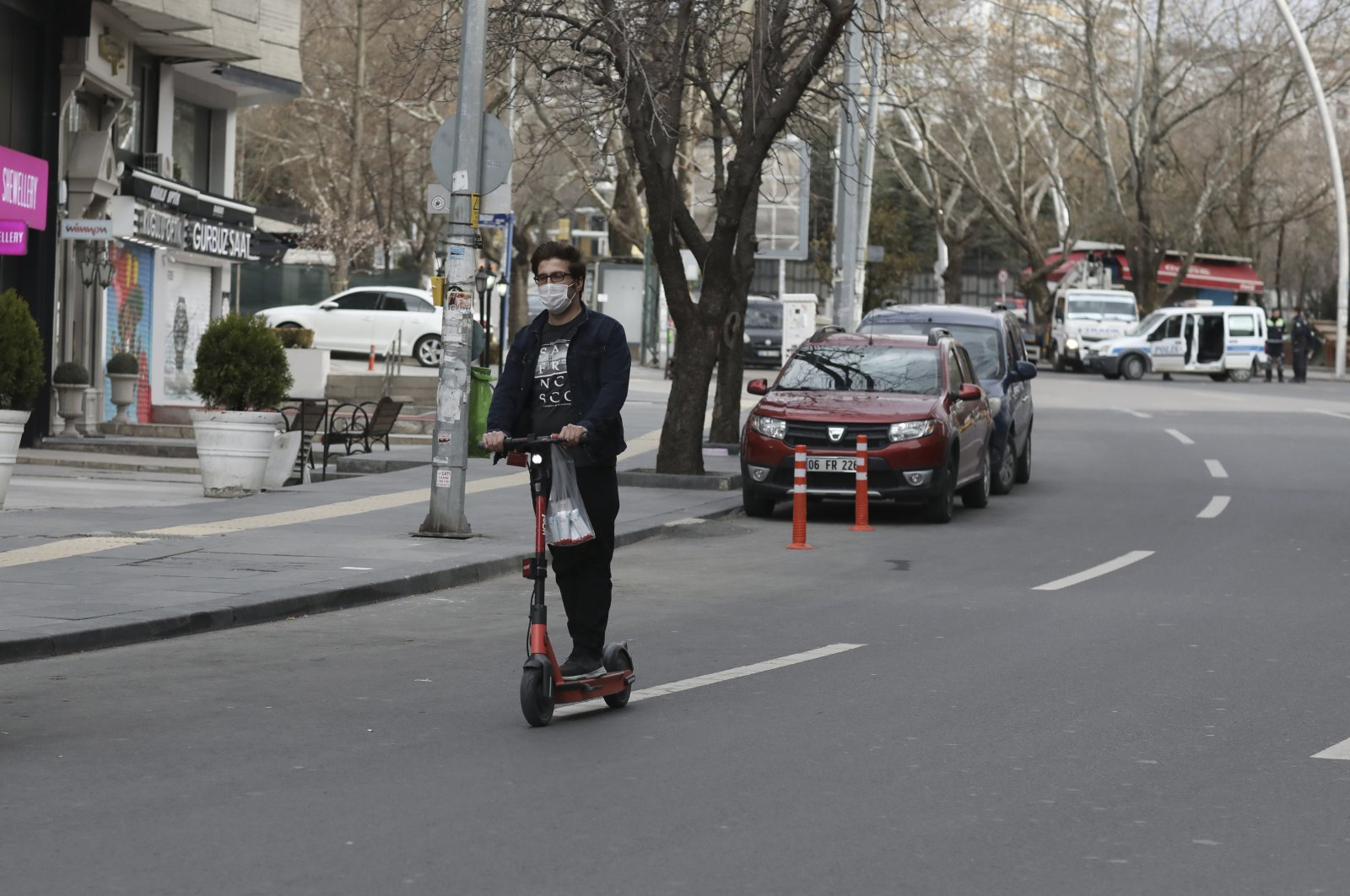 A man wearing a mask to help protect against the spread of coronavirus, rides a scooter down a nearly deserted popular street during a two-day weekend nationwide lockdown, in Ankara, Turkey, April 4, 2021. (AP File Photo)