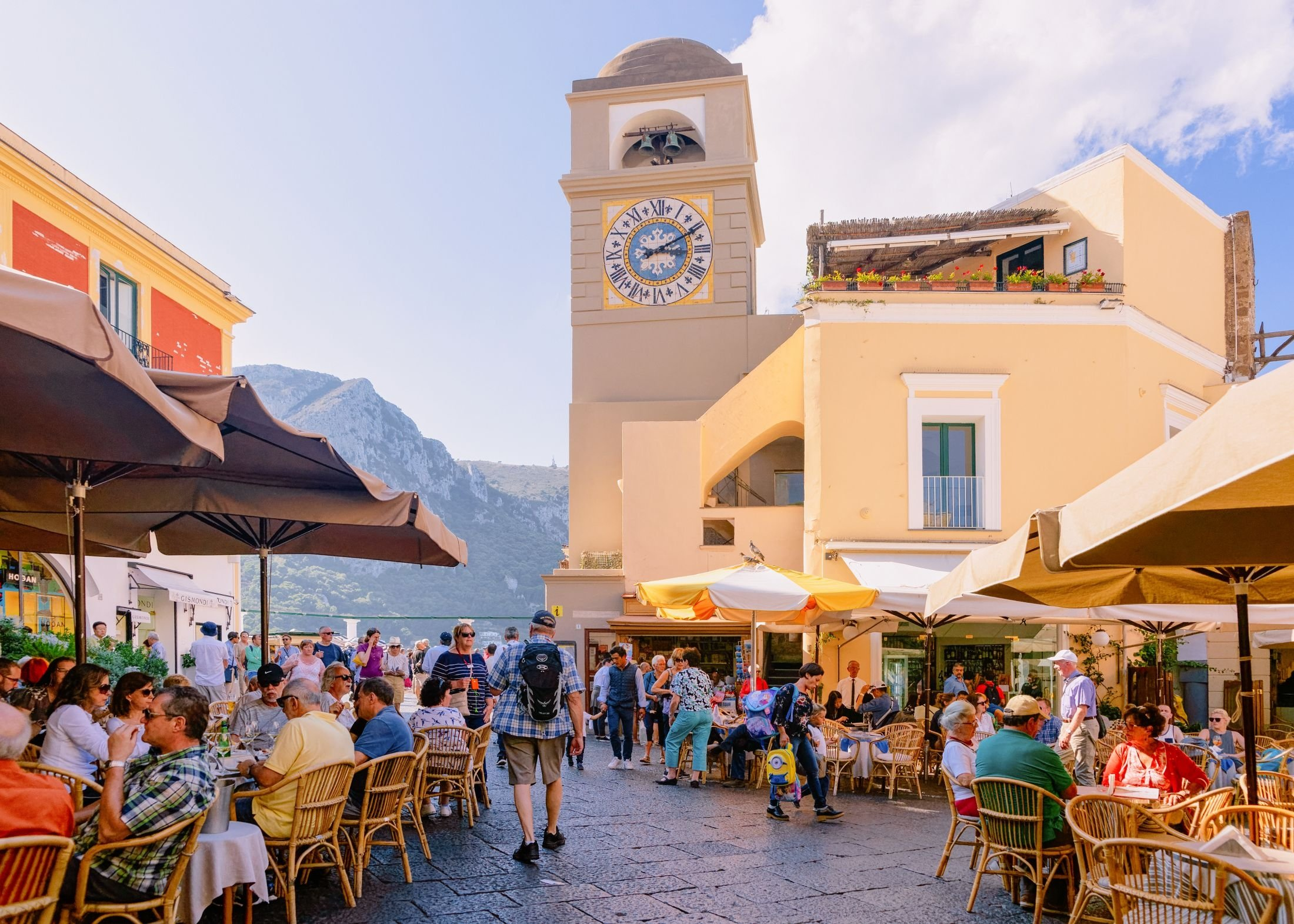 People sit and walk around at the Piazza Umberto I Square with Church of Santo Stefano in the background, on the island of Capri, Italy. (Shutterstock Photo)