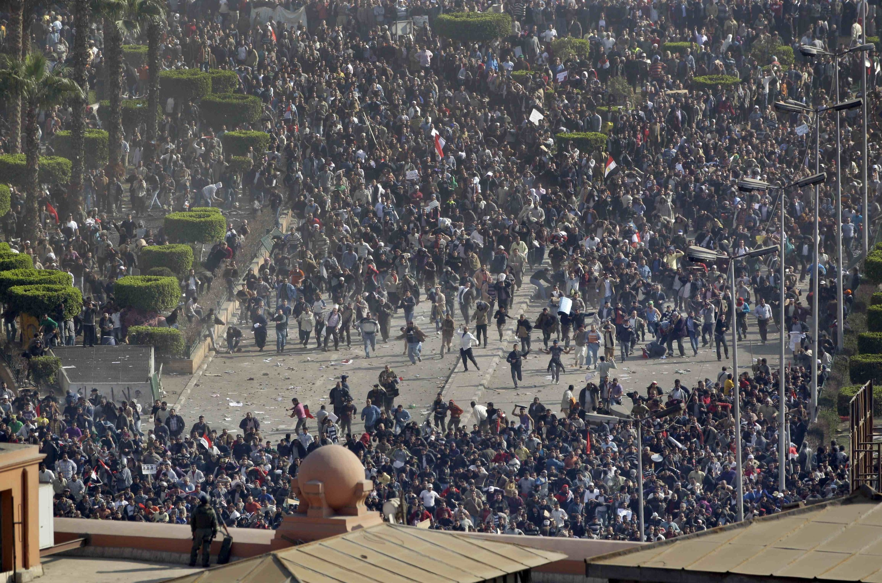 Pro-government demonstrators, foreground, clash with anti-government demonstrators as an Egyptian soldier on the rooftop of the Egyptian Museum observes the center of anti-government demonstrations at Tahrir square, Cairo, Egypt, Feb. 2, 2011. (AP Photo)